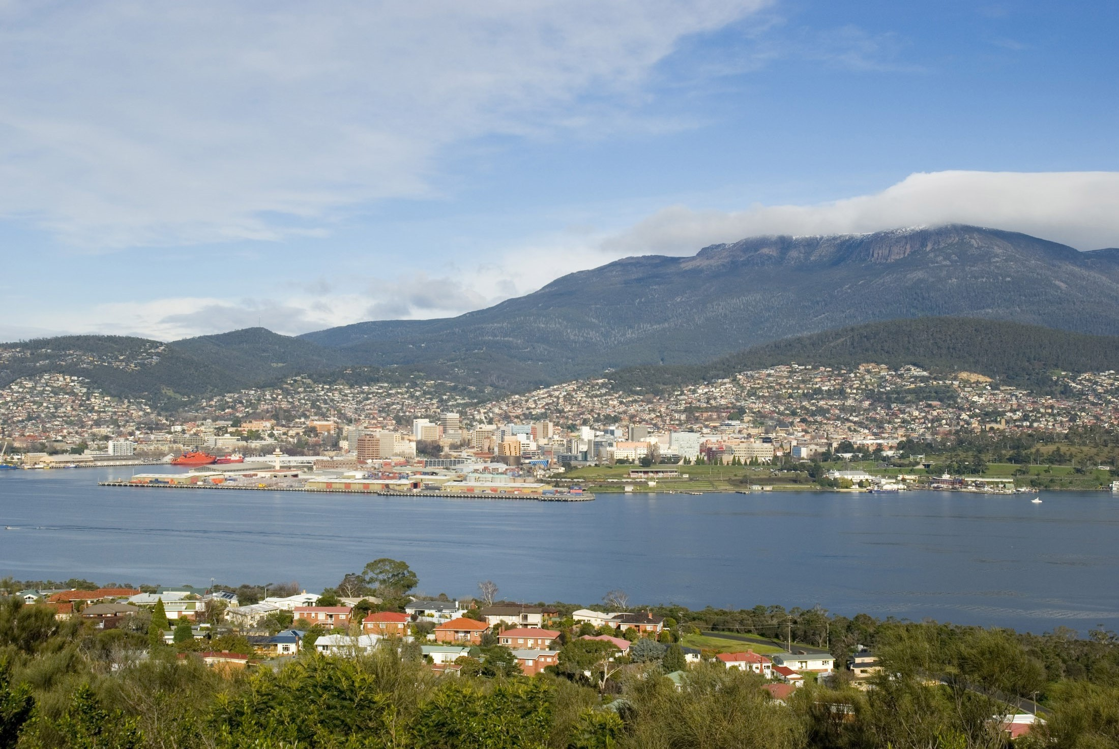 a panoramic view of hobart with mount wellington shrouded in cloud to the rear