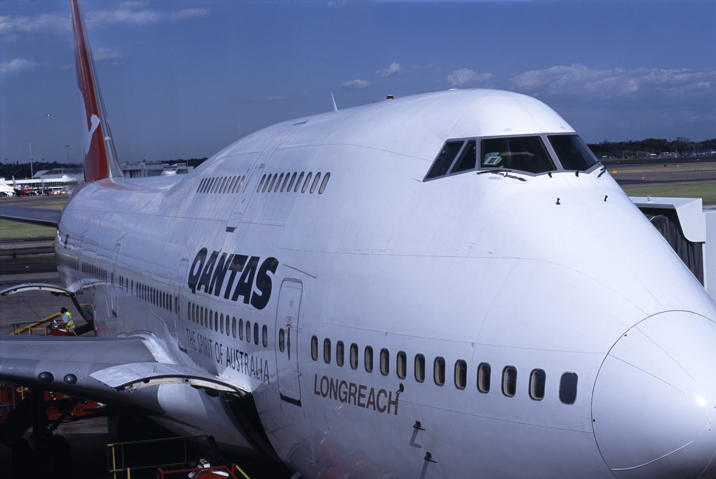 Qantas passenger airplane on the apron at an airport refueling and embarking passengers for an international flight, close up view of the front and pilots cockpit