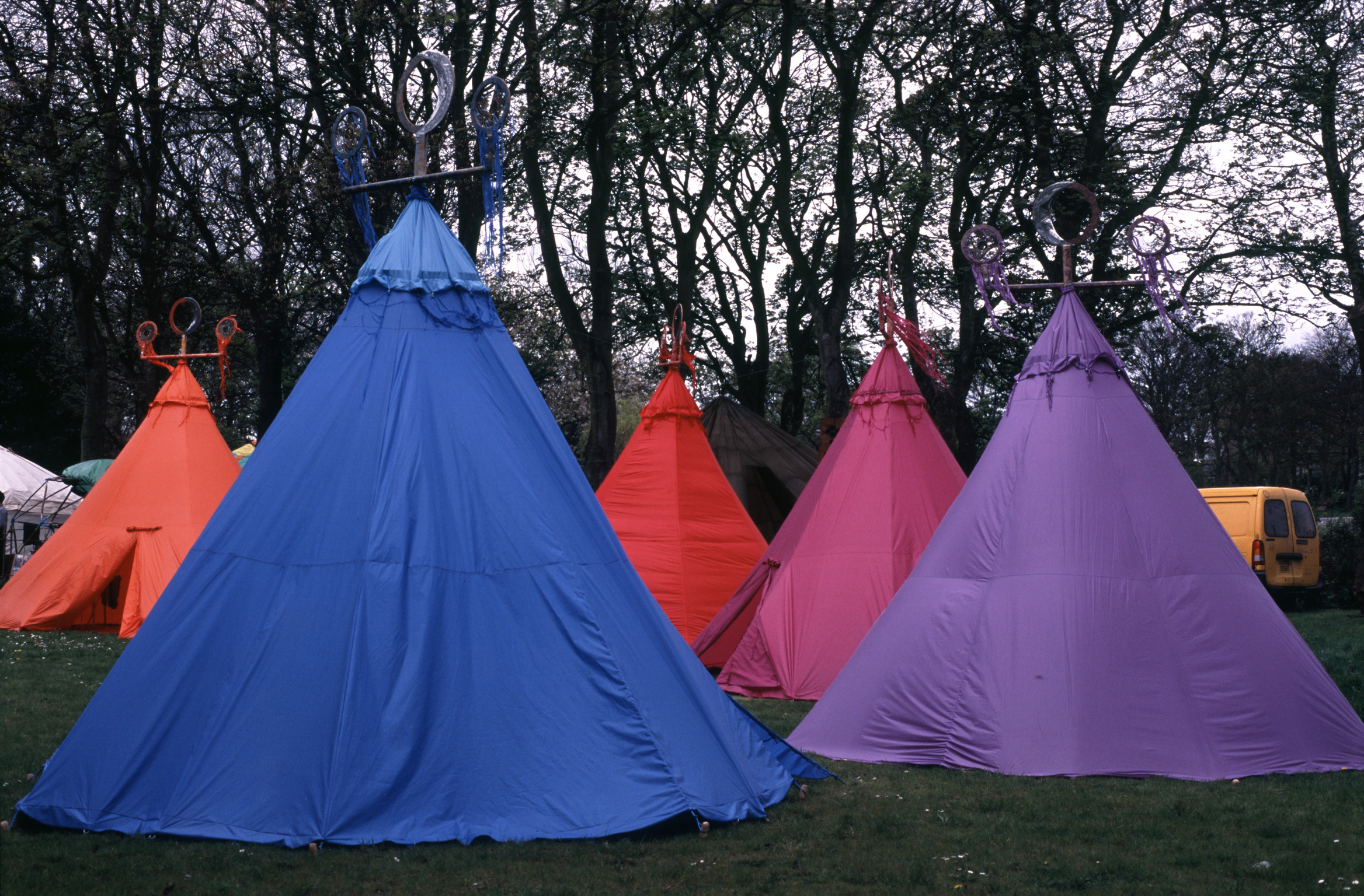 Group of colorful blue, orange and pink tents pitched on a wooded campsite conceptual of a vacation, travel and healthy lifestyle