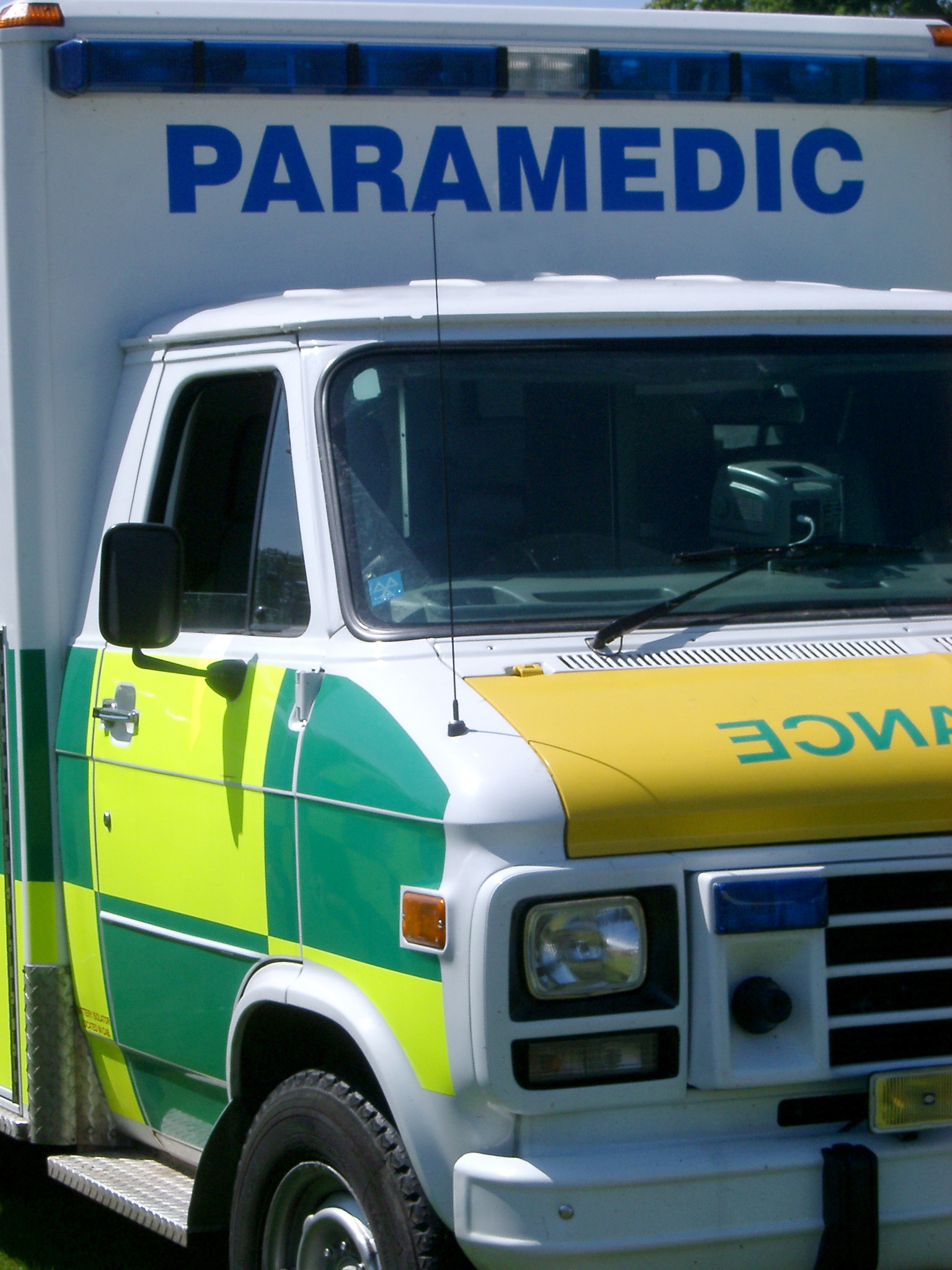 Close up detail of an ambulance showing the brightly colored signage on the door and large sign above the cab roof saying - Paramedic