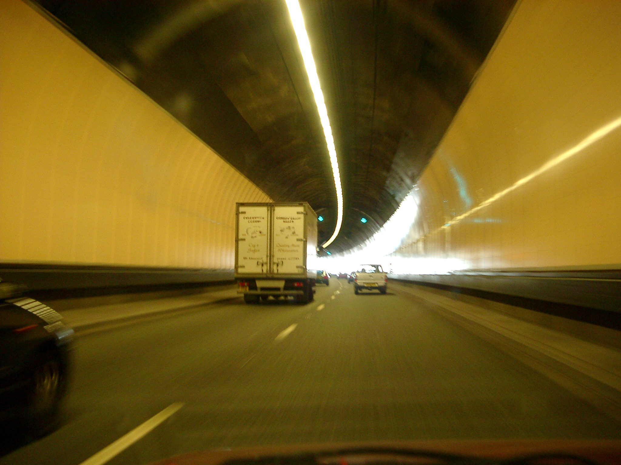 Interior of a road tunnel with traffic with cars and trucks passing around a curve in the road