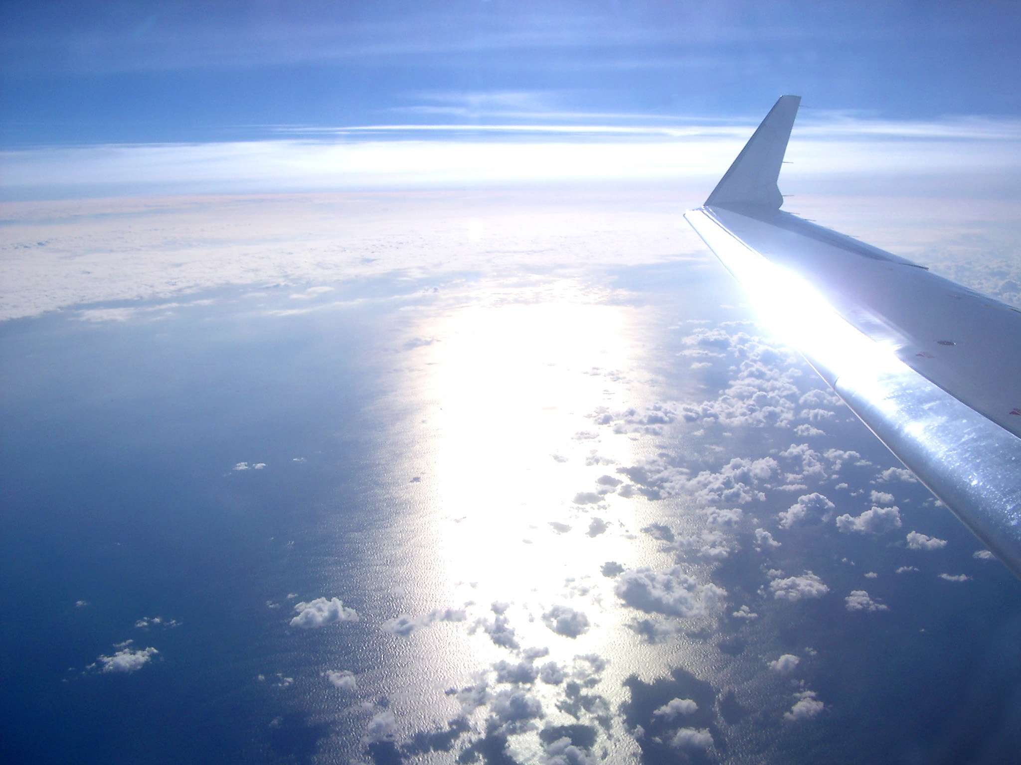 Wing tip of an airplane flying over cloud with a beam of bright sunlight in a travel, flying and vacation concept