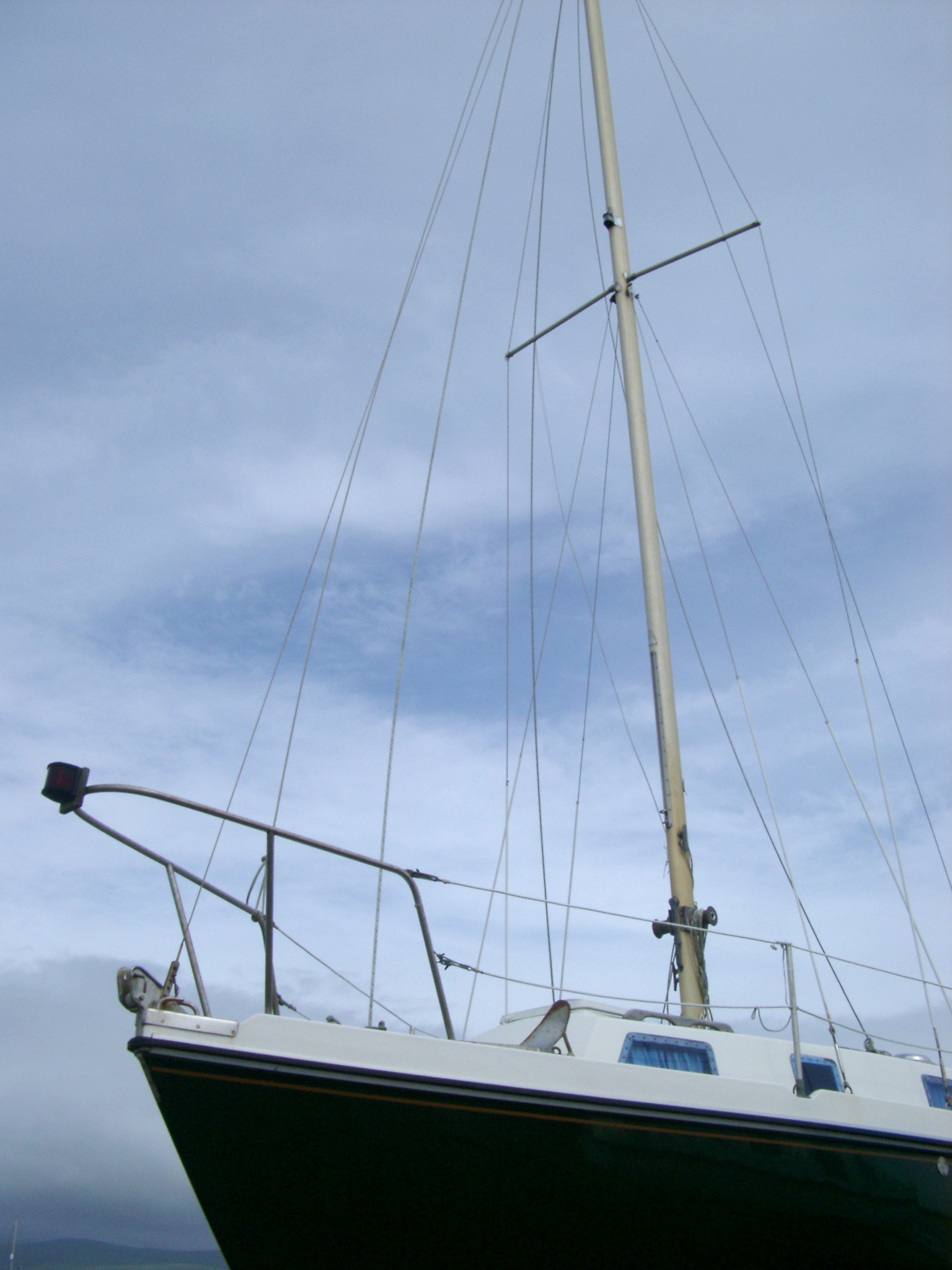 Yacht forecastle with a closeup view showing the bow and front mast with its rigging and stays against a cloudy sky