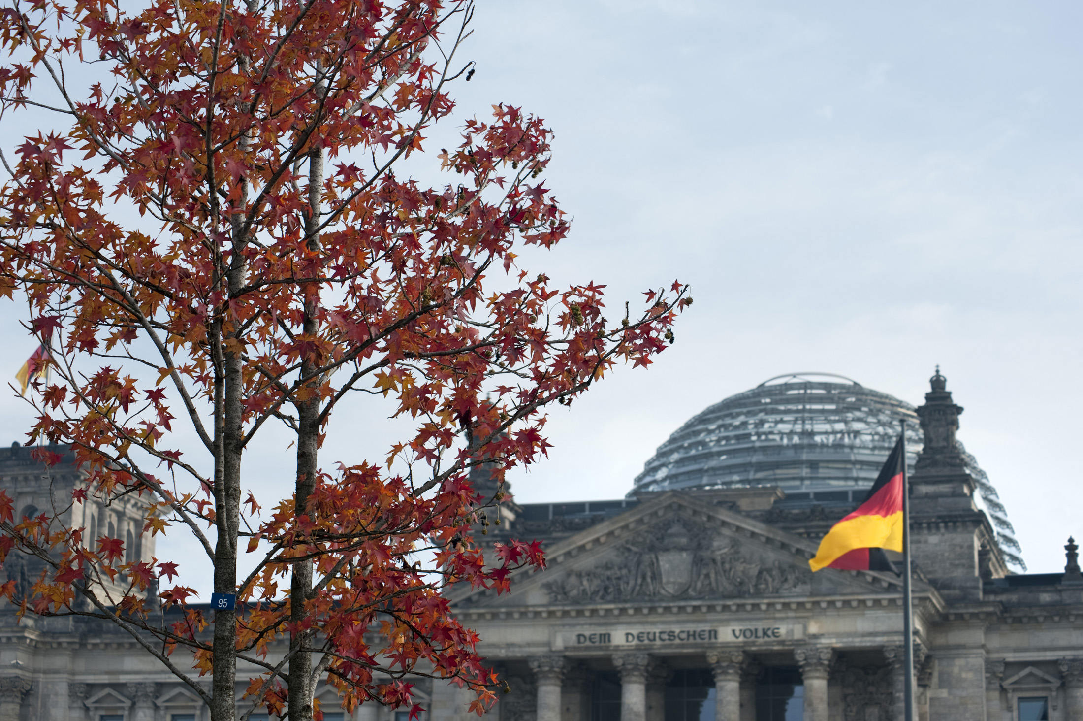 the reichstag parliament building in berlin with a german flag in the distance