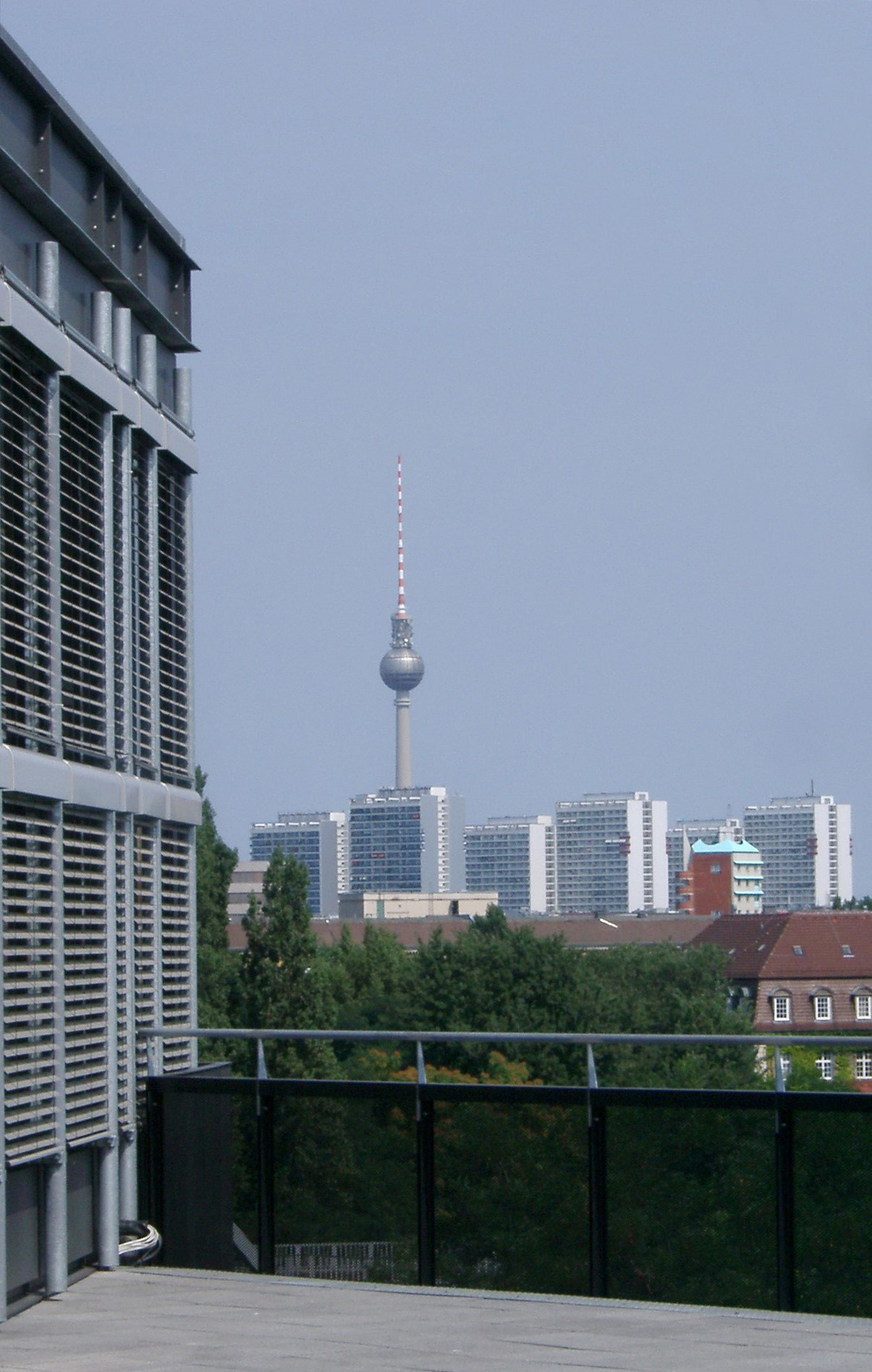 View of high-rise architecture in Berlin with the Fernsehturm TV tower and antenna towering above them