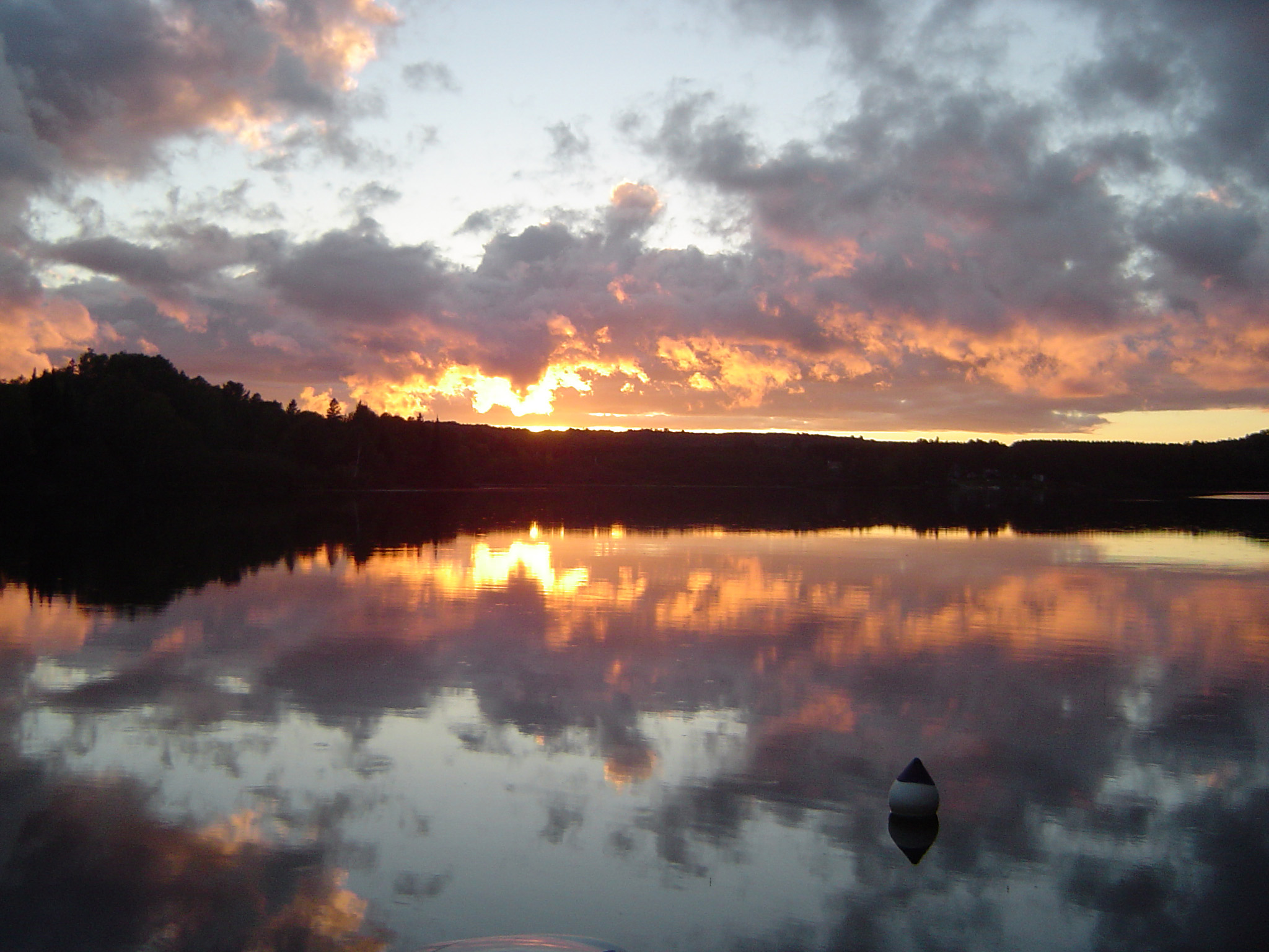 Beautiful sunset reflected in one of the numerous lakes in the Algonquin Provincial Park in Canada with a fiery sky and delicate pink clouds