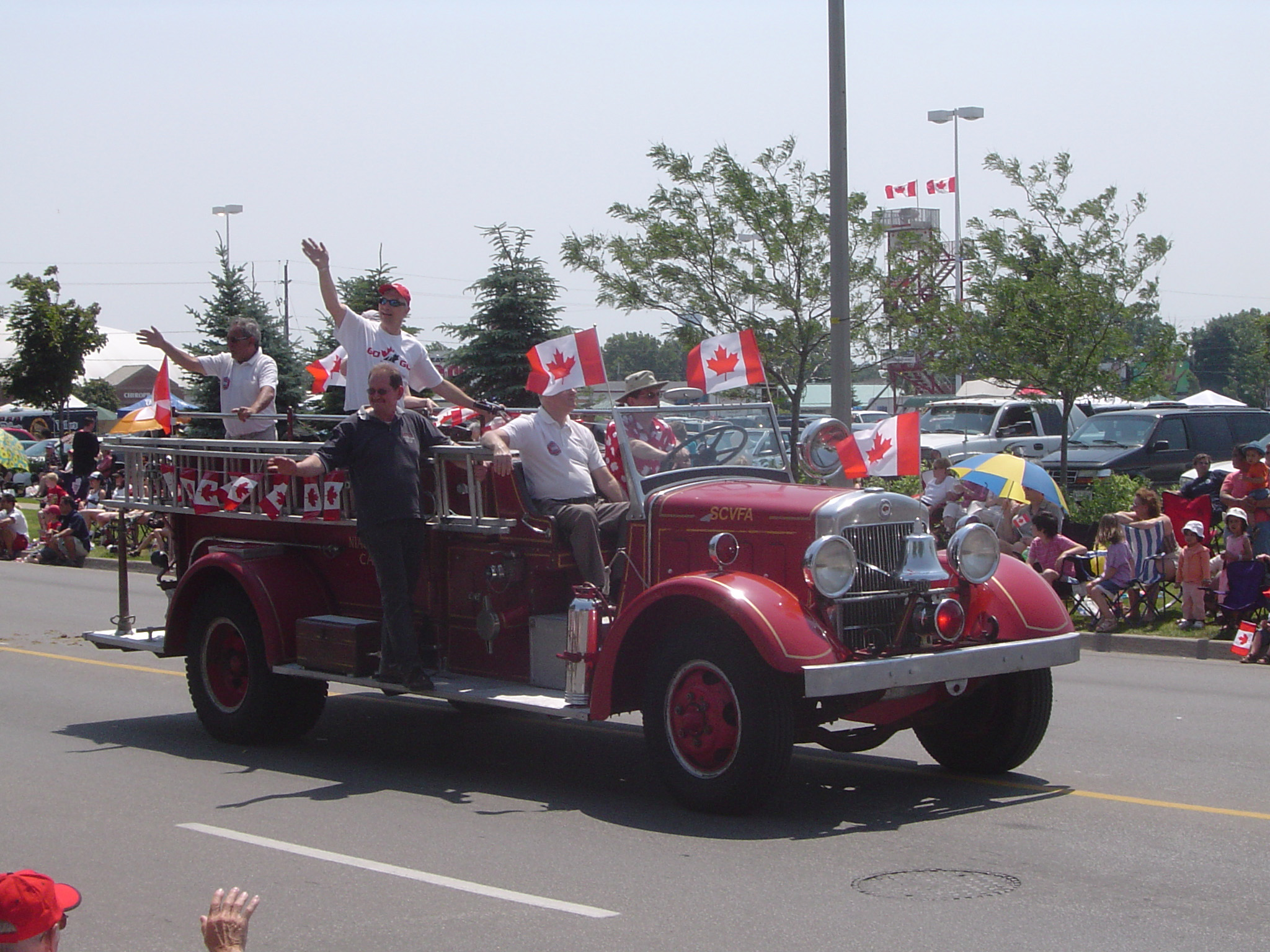 Historic vintage Canadian fire truck driving through the streets with firefighters waving at seated crowds watching the parade
