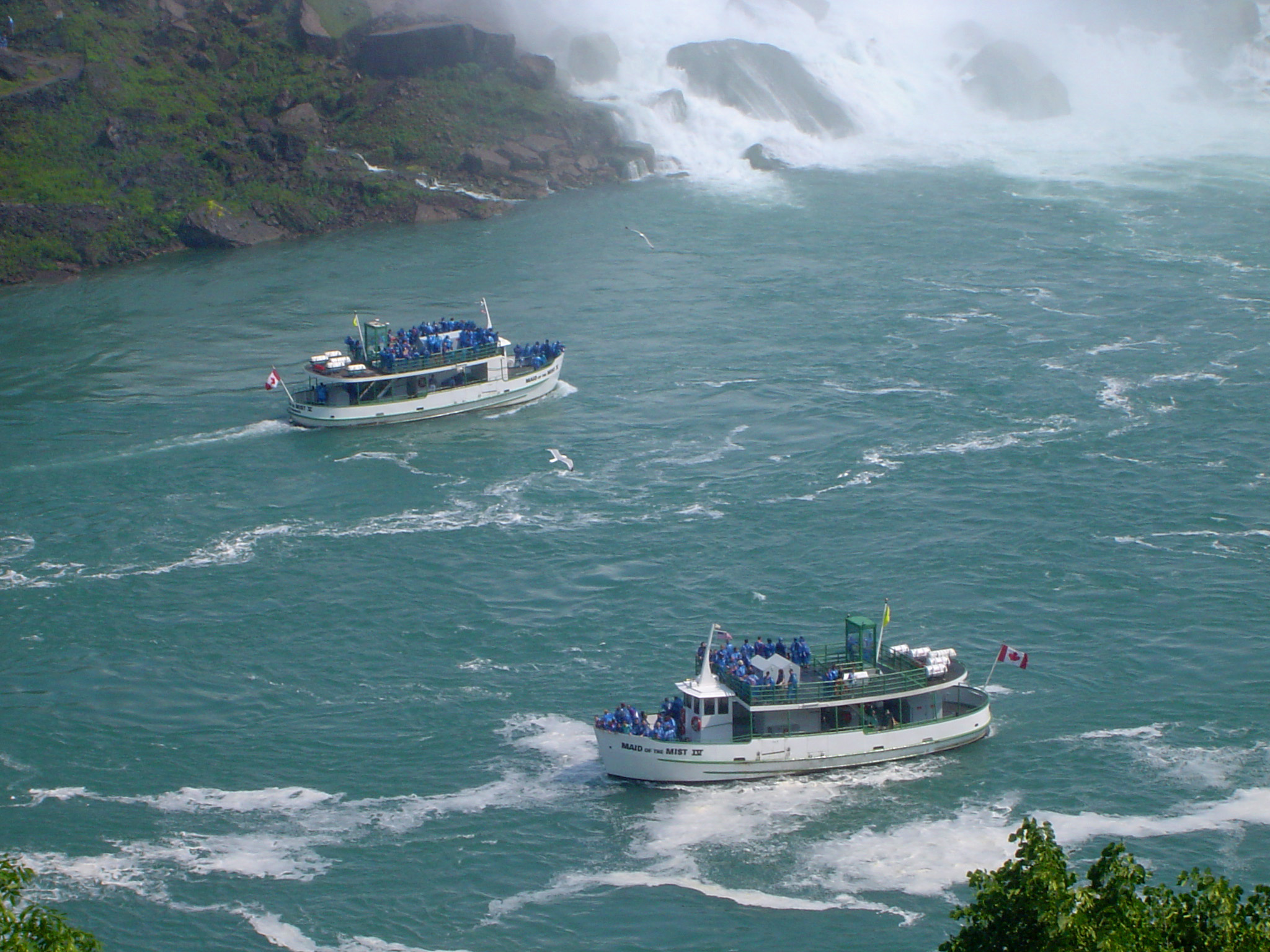 Tourist boats at the foot of the Maid of the Mist Niagara Falls between Canada and the USA with the spray from the waterfall visible in the background