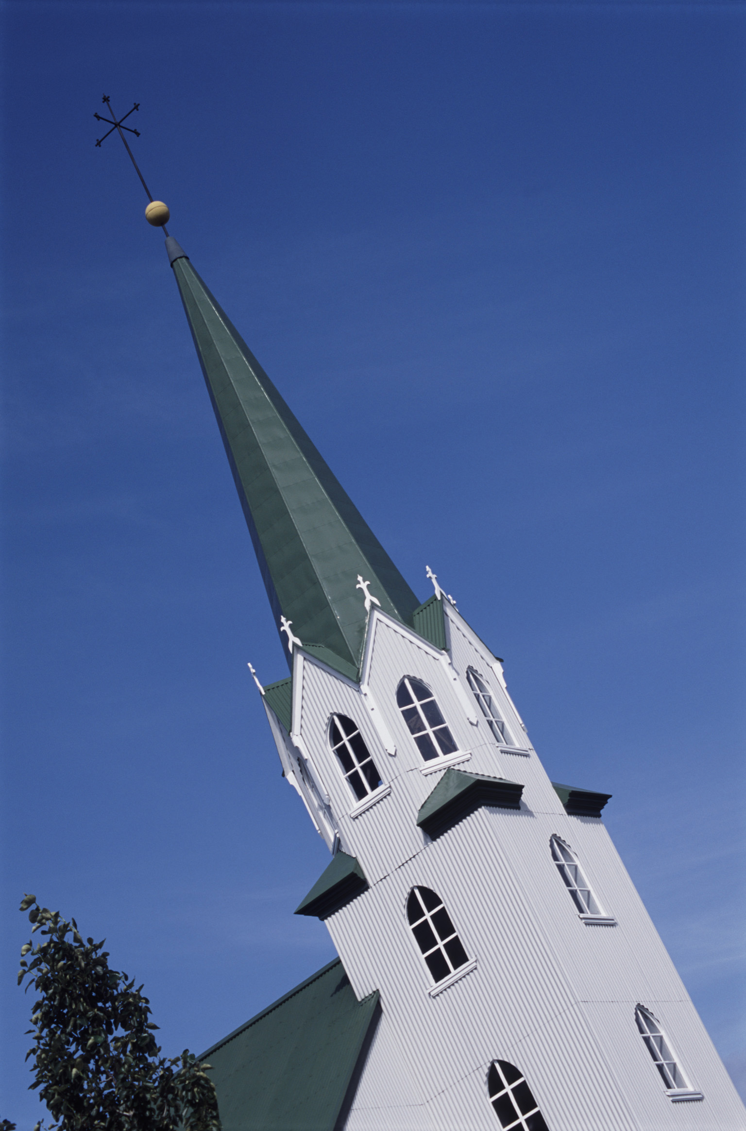 Elegant church spire in Reykjavik , Iceland, with traditional architecture of a corrugated iron roof against a blue sky