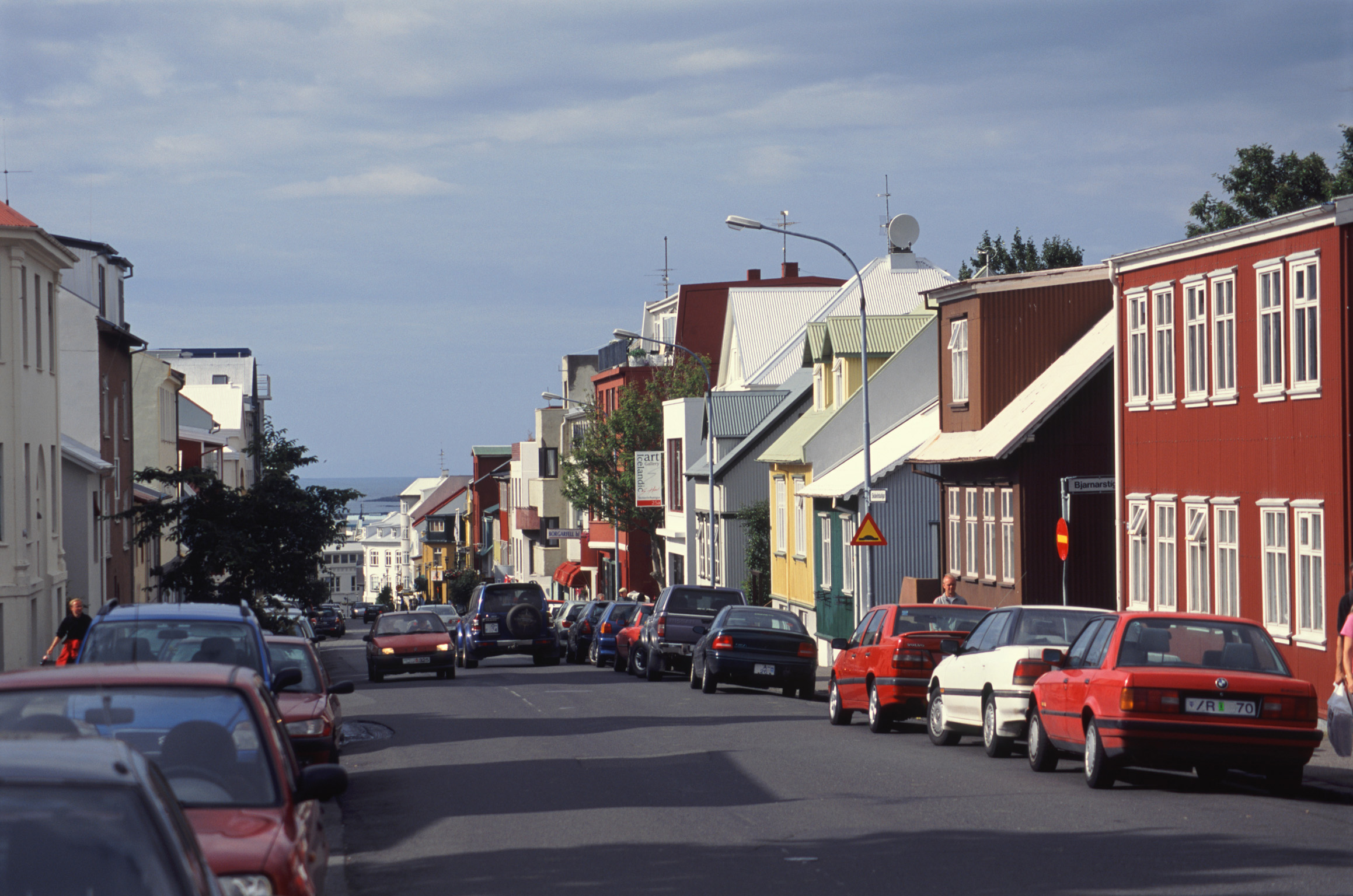 Street scene in Reykjavik, Iceland with traditional architecture and rows of parked cars on a sunny day
