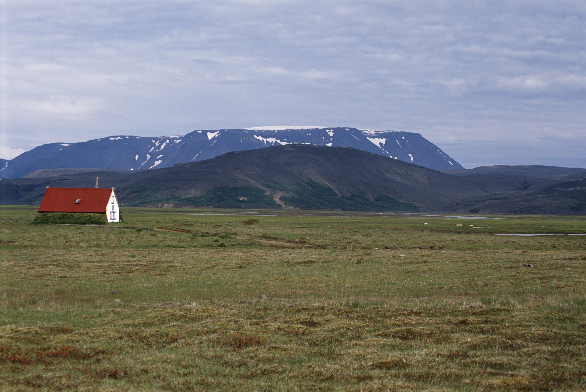 Remote red roofed hut in Iceland standing in open grassland with distant snow covered mountain peaks