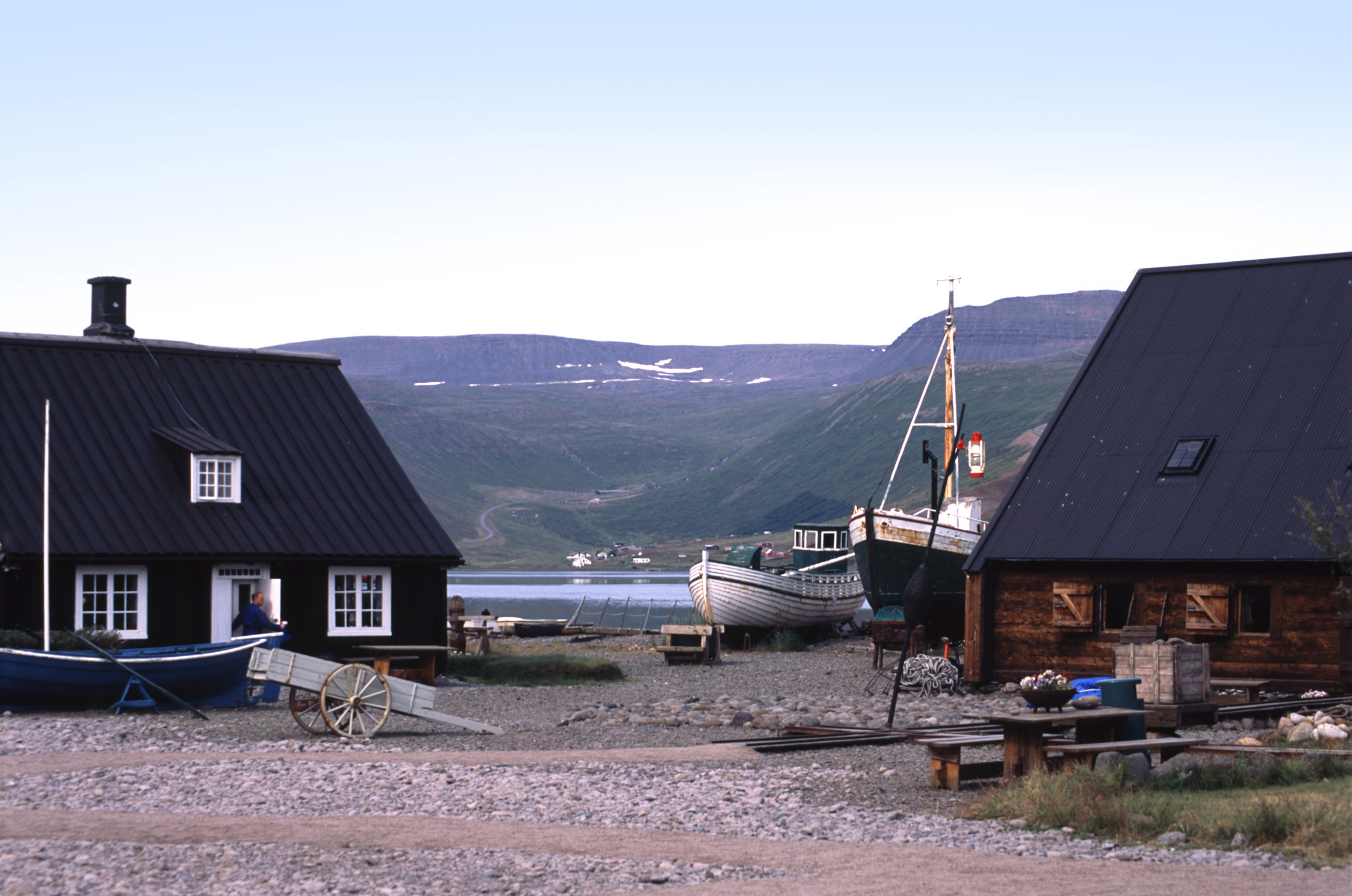 Iceland village on the edge of a bay or meltwater lake with fishing boats pulled ashore on the sand between the cottages
