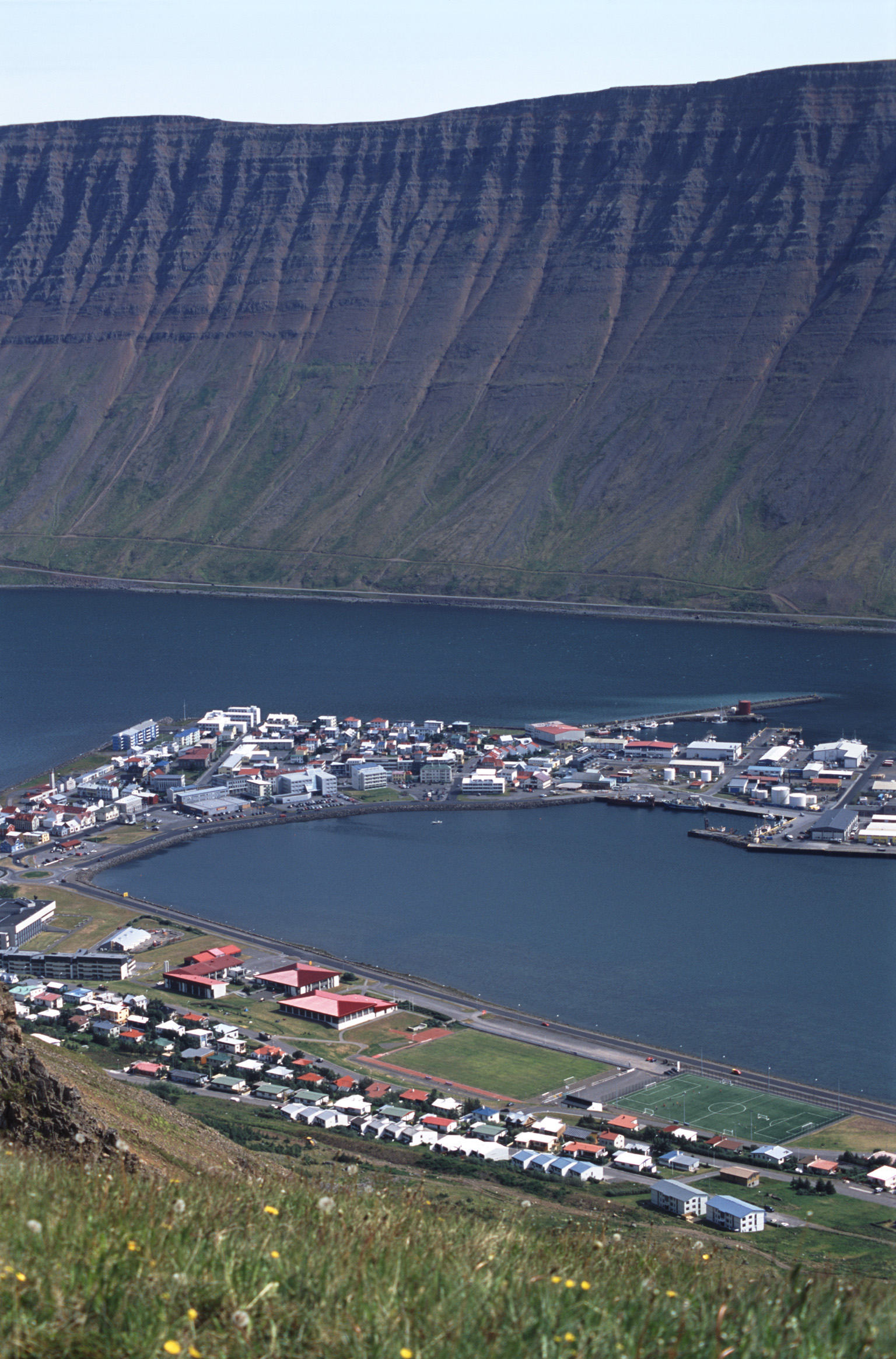 Scenic landscape aerial view of Isafjordur in Iceland, a remote fishing town in the fjords nesting under a volcanic mountain peak at the edge of a bay