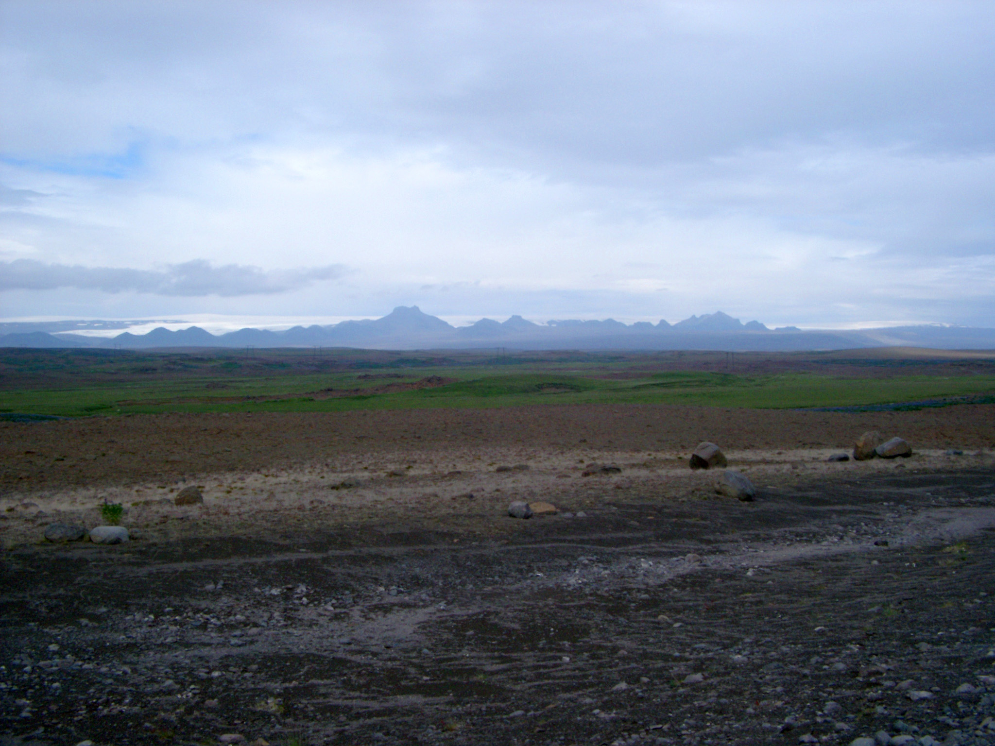 Remote Icelandic landscape with a stony path leading past a river with a range of volcanic mountain peaks in the distance