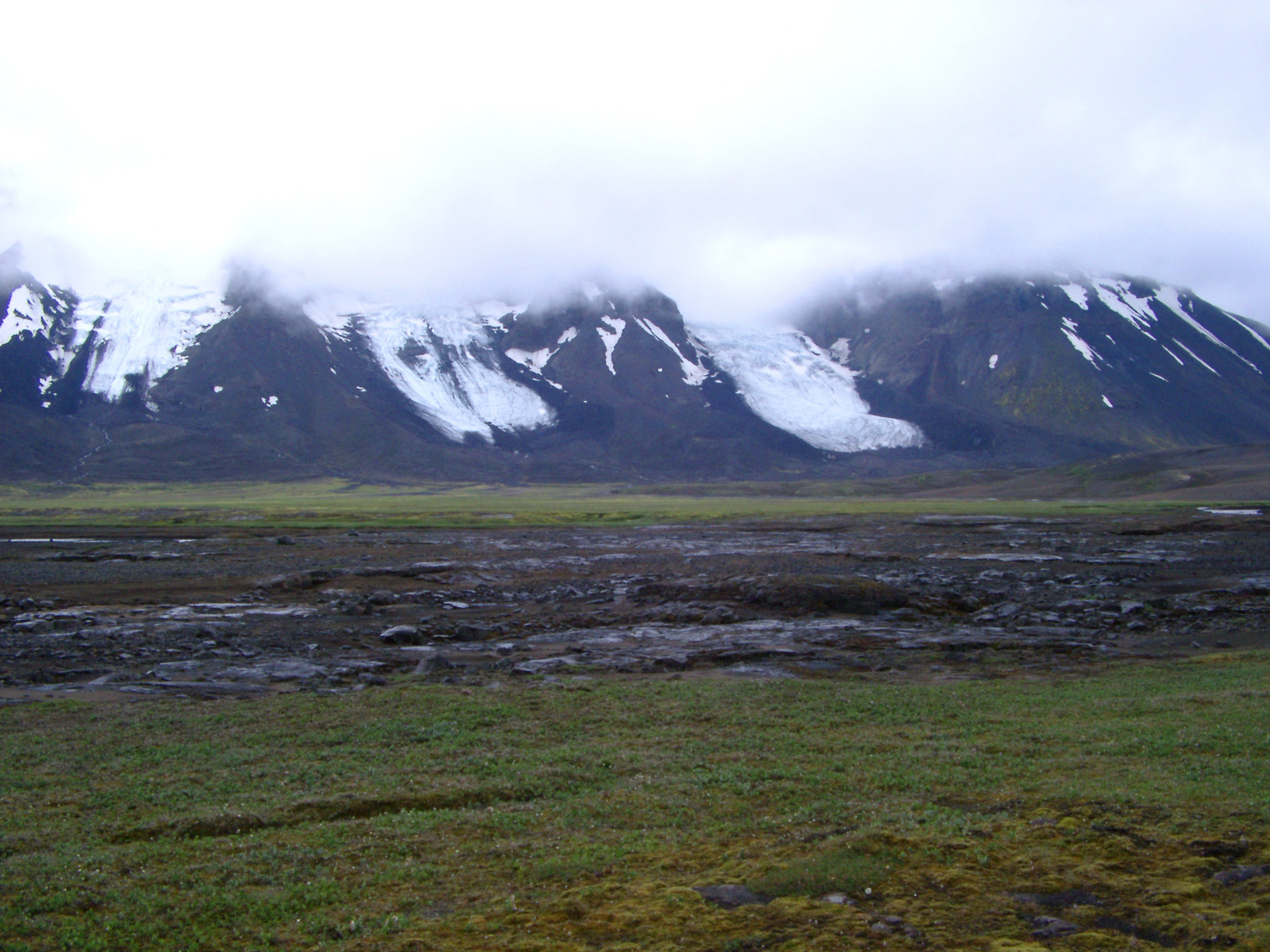 Ice flows or glaciers on a volcanic mountain peak shrouded in mist and cloud in Iceland