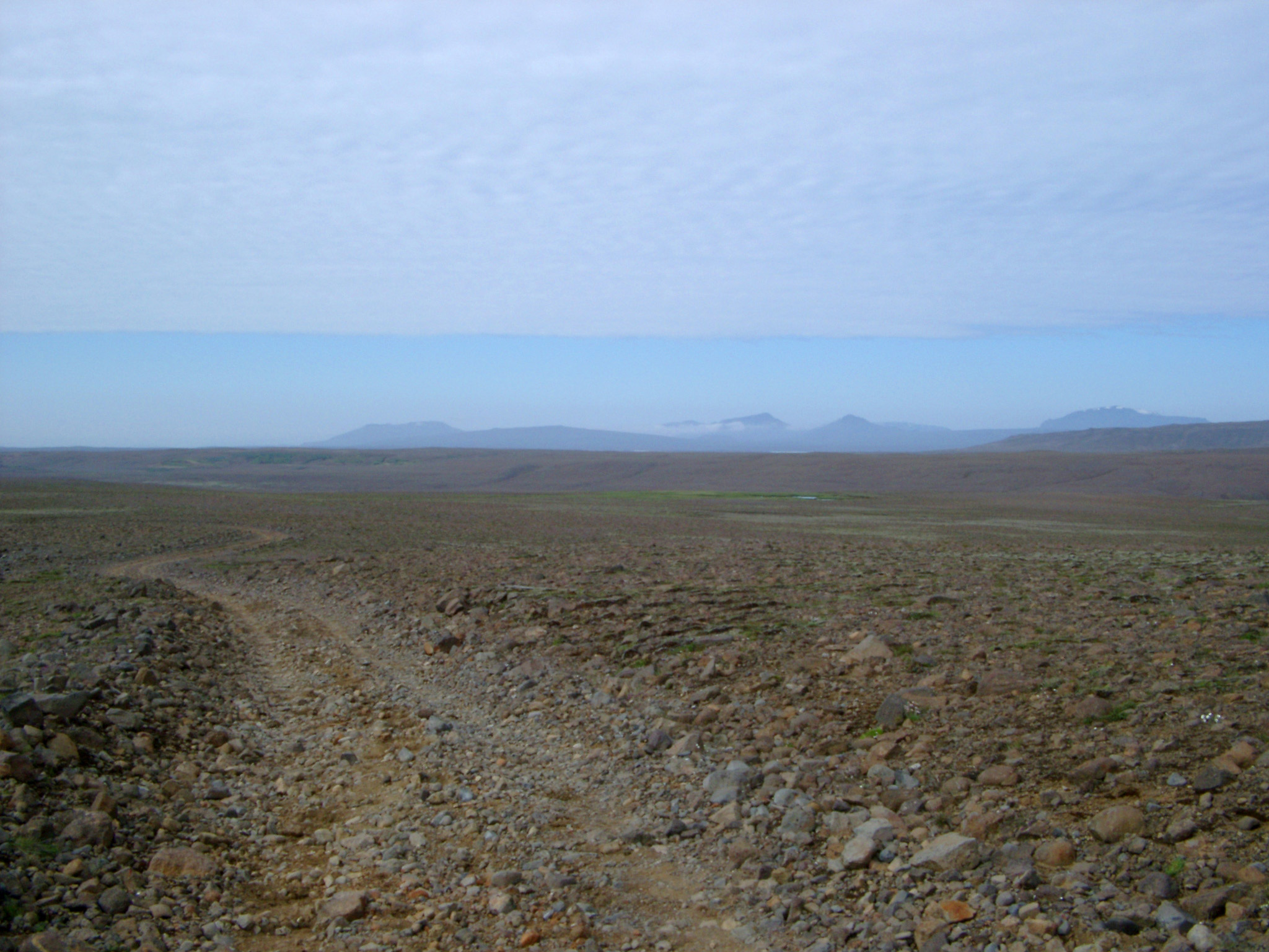 Iceland Path on Wide Brown Field Isolated on Light Blue Sky Background.