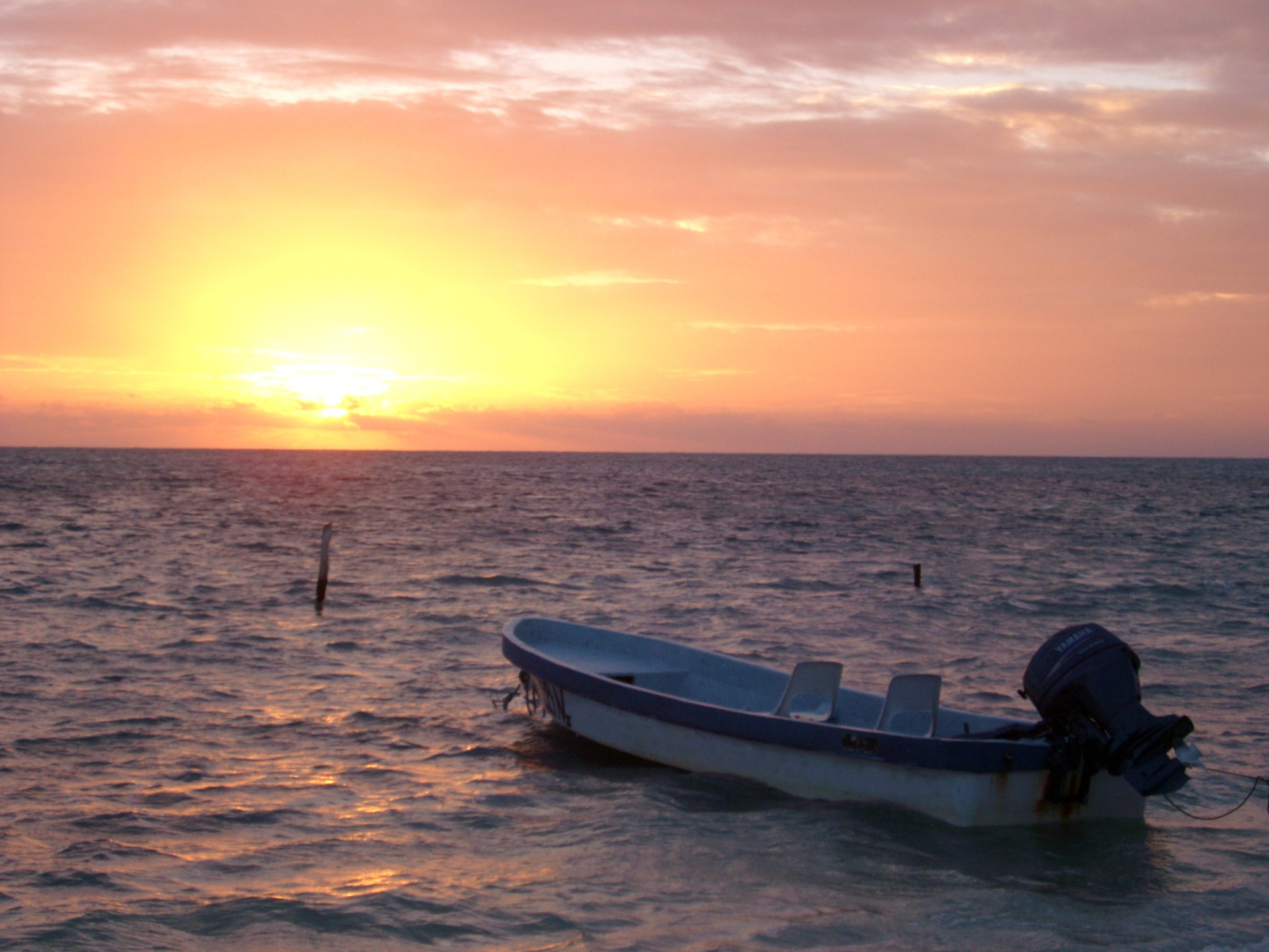 Colorful Caribbean sunset with a glowing orange sun dipping below the ocean and a moored wooden motorboat in the foreground