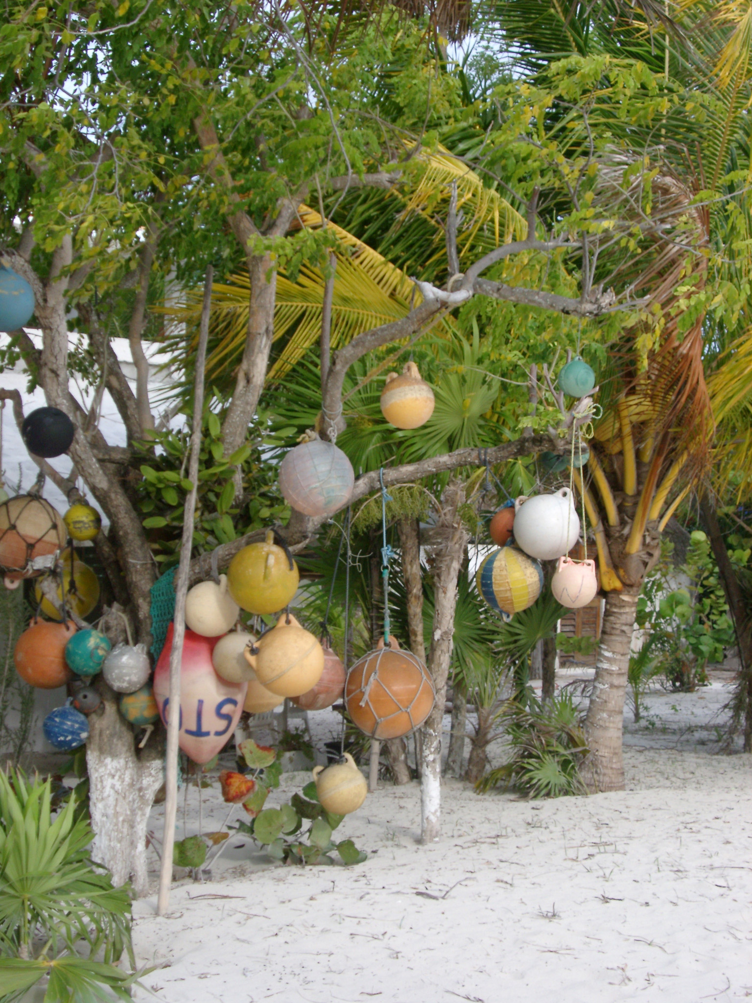 Colorful plastic fishing floats hanging from a wooden frame below palm trees on the golden sand of a tropical beach
