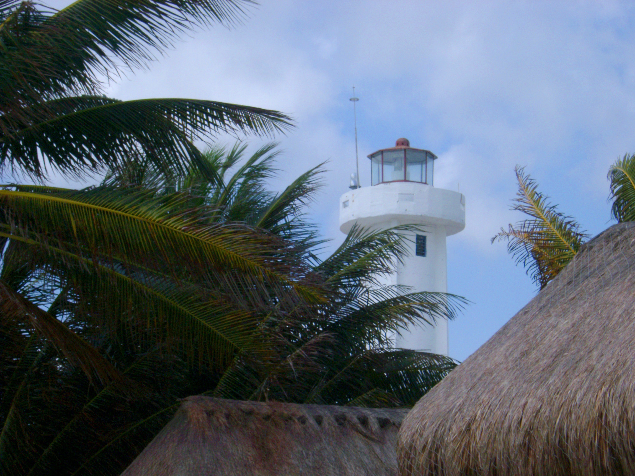 Lighthouse surrounded with palm trees viewed over the thatched roofs of beach cottages in Mexico