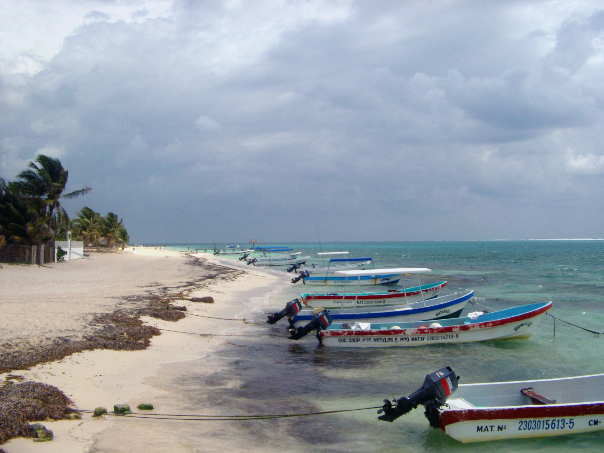 Small motorboats moored to the shoreline in Mexico with their bows pointing out to sea on a golden tropical beach under a cloudy summer sky