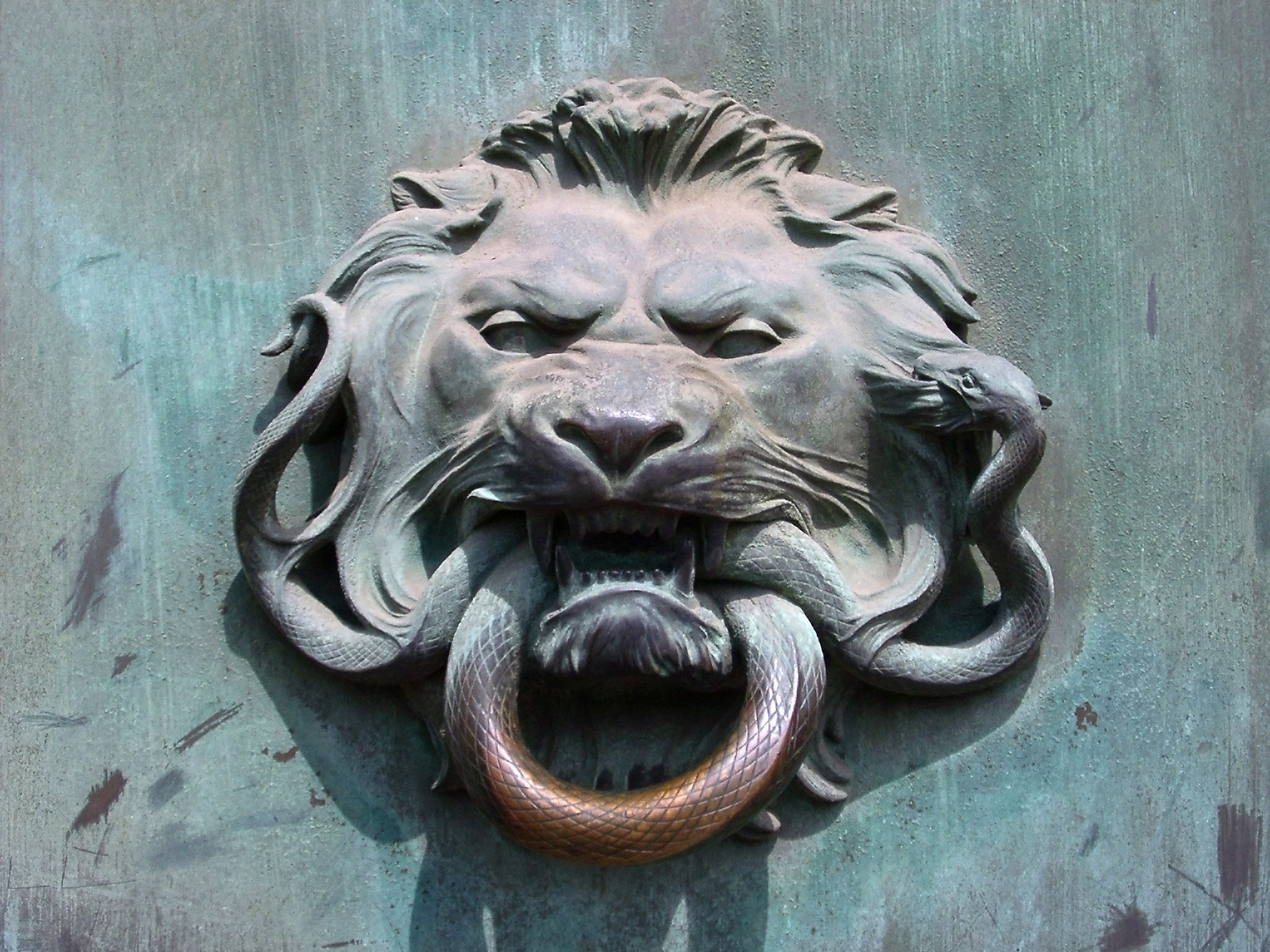 Detail of a door knocker of a lions head with a ring in its mouth on a door in Paris