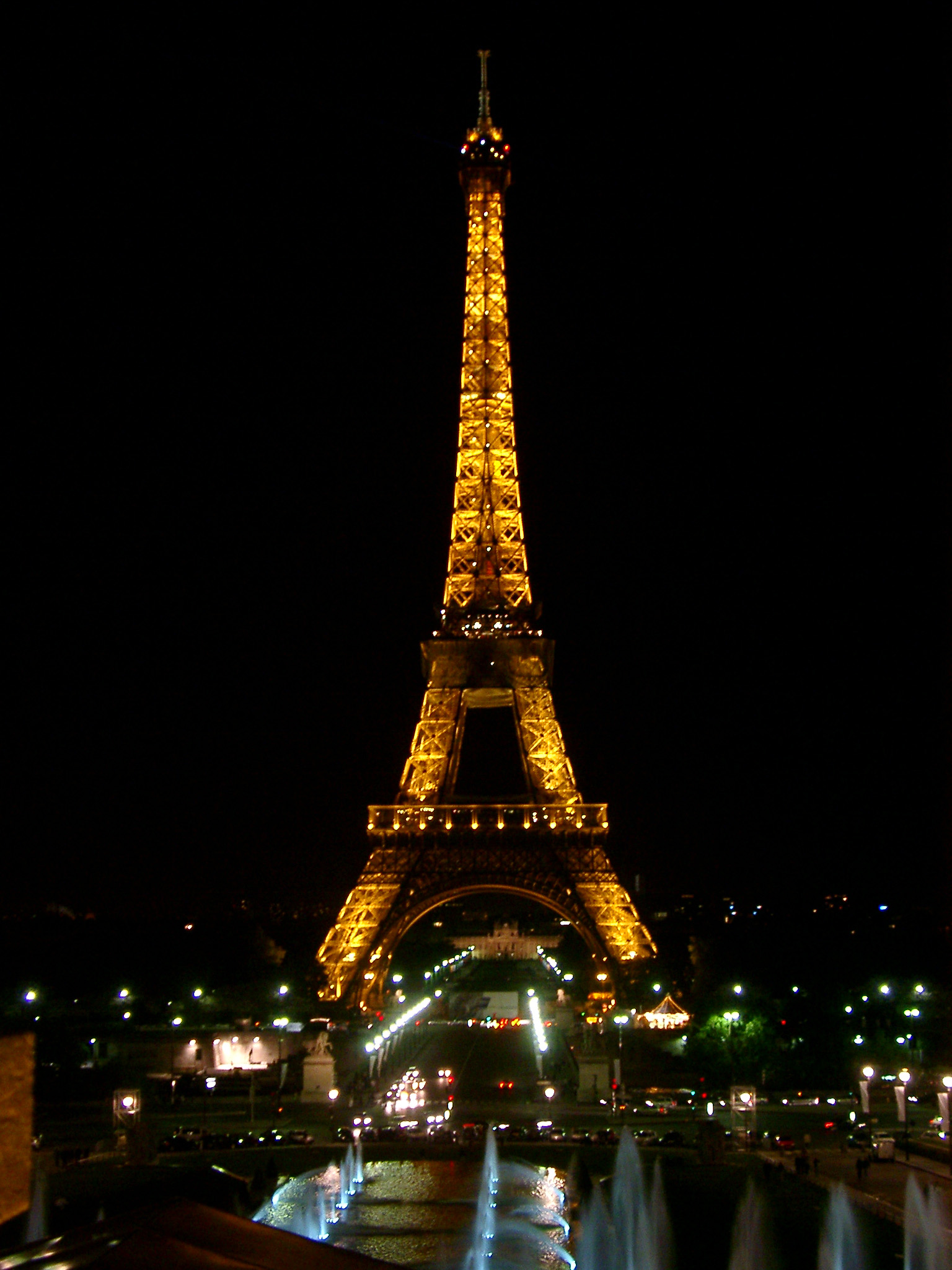 Eiffel Tower, Paris, illuminated at night showing the lighting display on the iron girders against a dark night sky