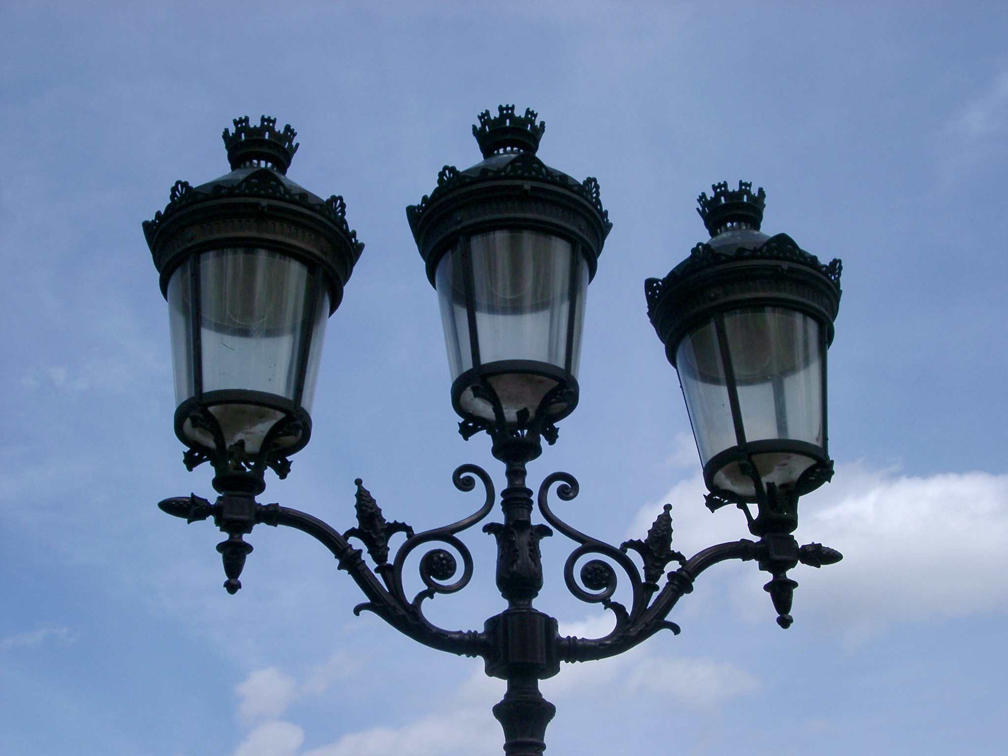 Paris lamppost with three lanterns in a typical Art Nouveau style of scrolling leaves against a cloudy blue sky