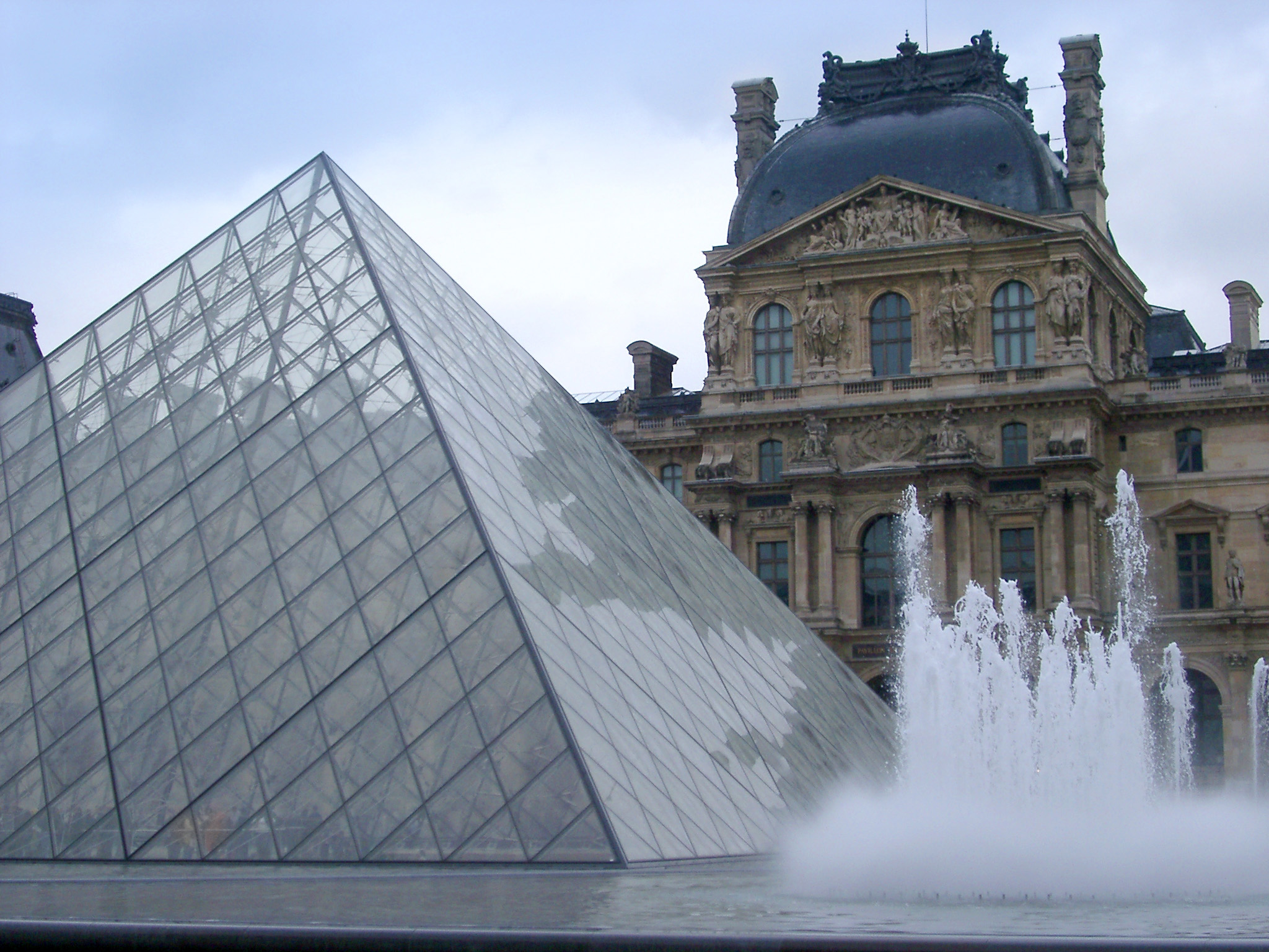 The glass pyramid at the Louvre, Paris with the ornamental fountains and external facade of the museum behind