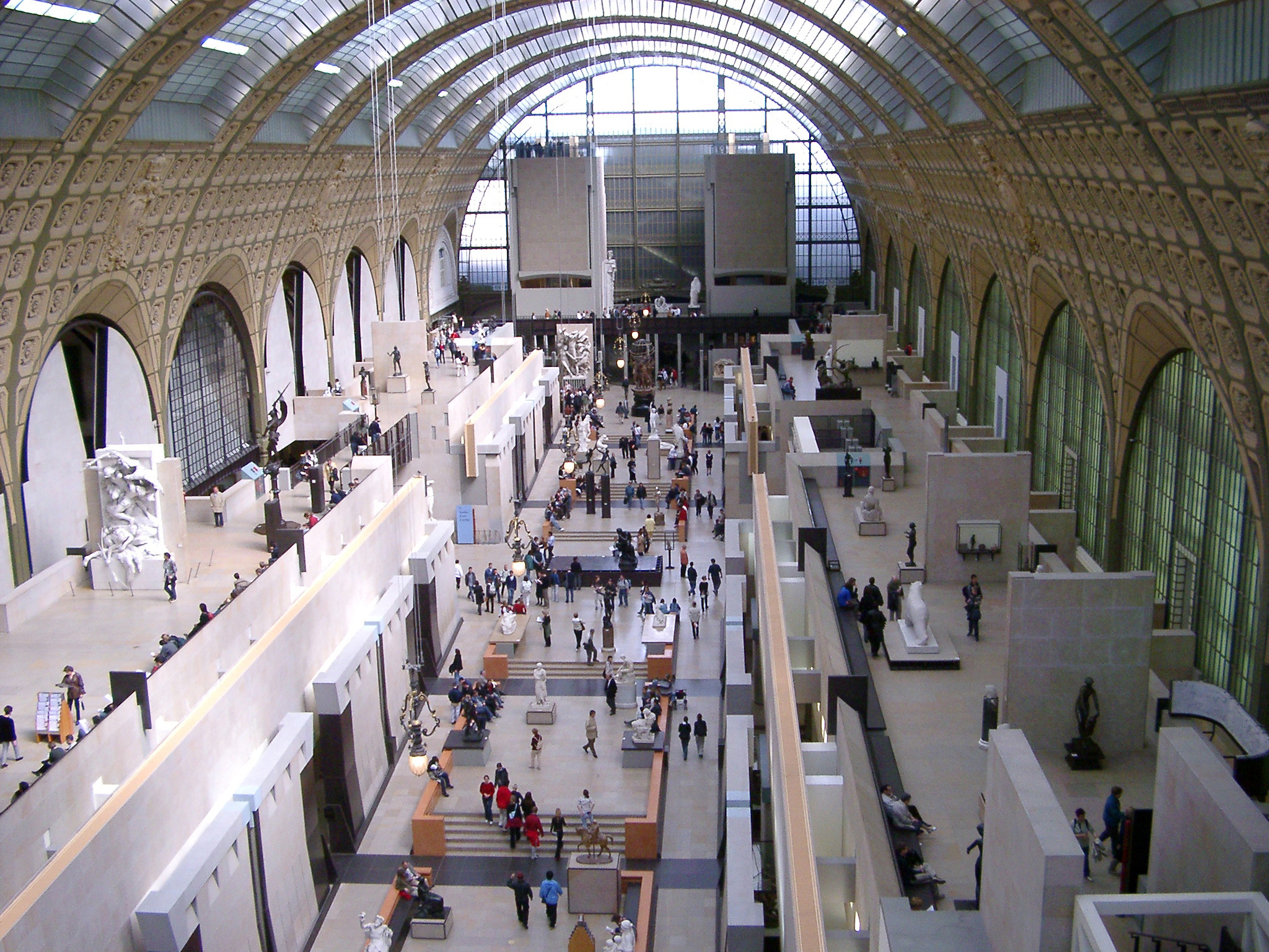 View along the interior central gallery filled with people at the Musee de Orsay, Paris