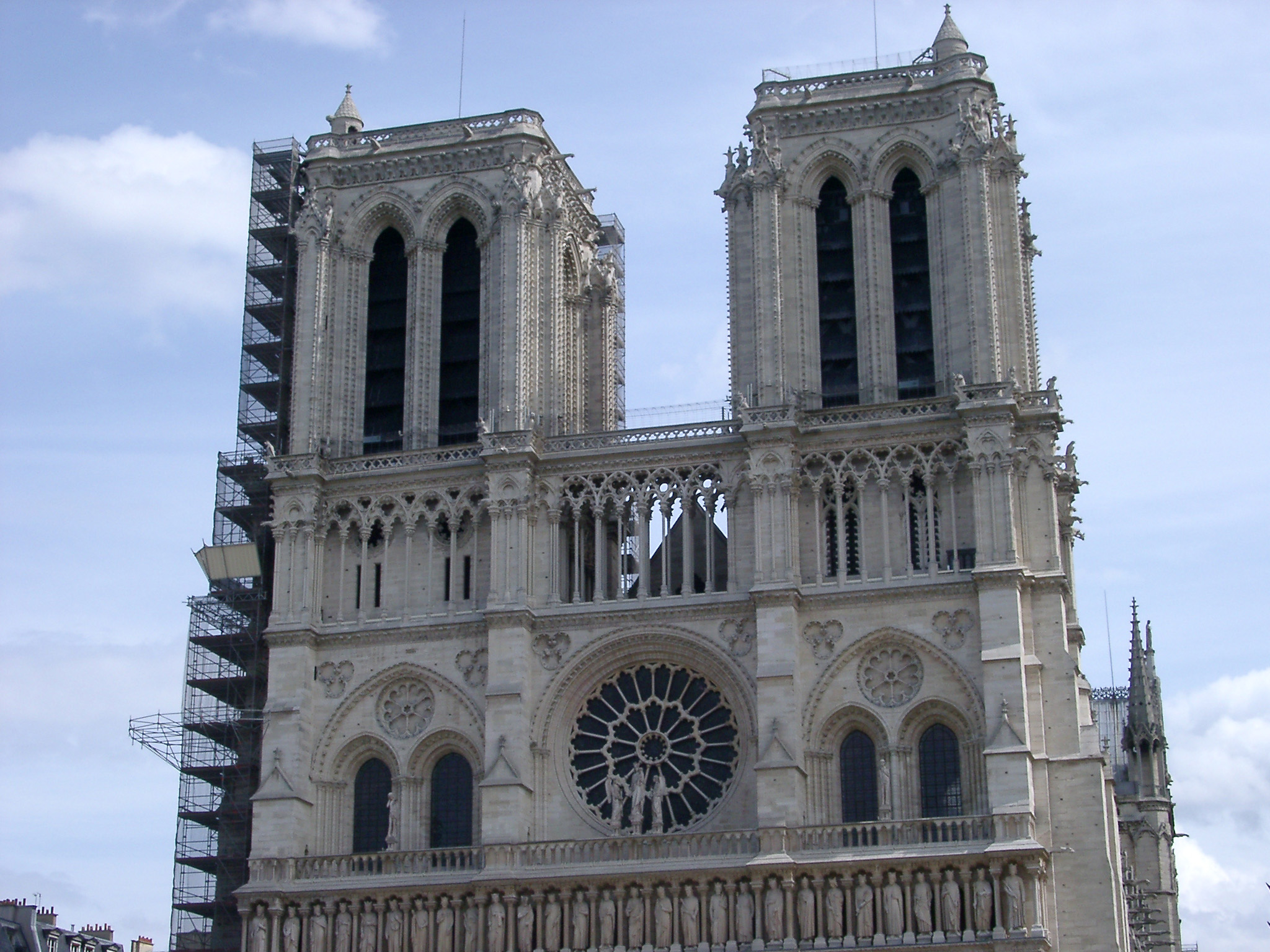 View of the historical front facade of the Notre Dame Cathedral in Paris, France against a blue sky