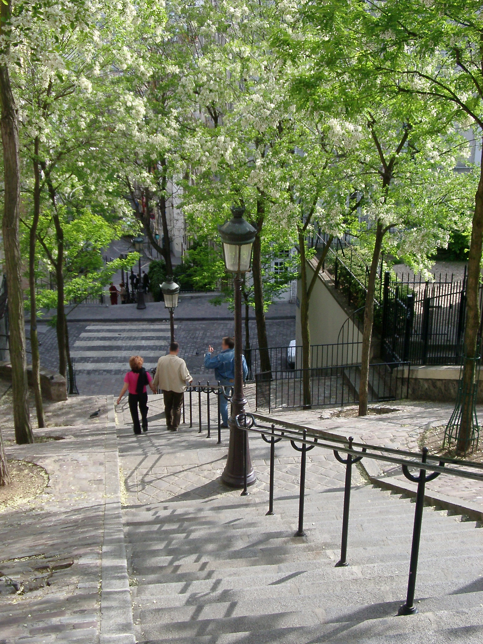 People walking down the long flight of steps leading down from butte Montmarte and the Sacre Couer Cathedral in Paris