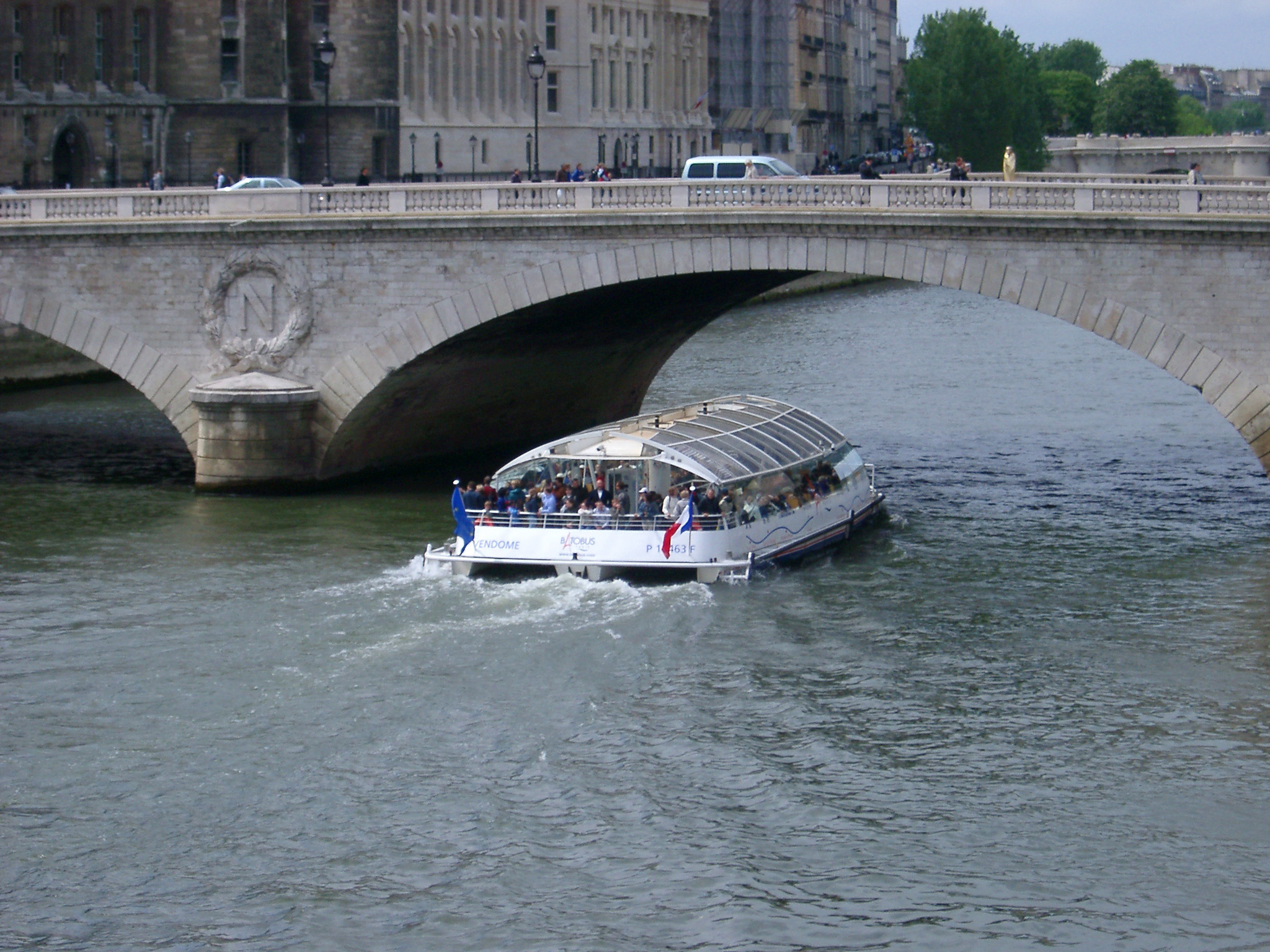 Tour boat or ferry passing under a bridge with traffic on the River Seine in Paris