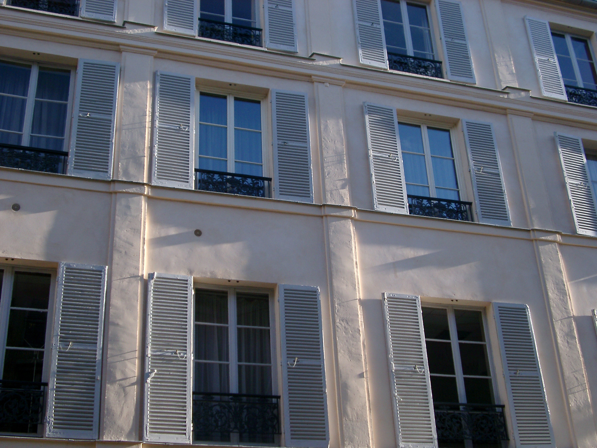 View of the facade of a Paris townhouse with slatted wooden window shutters on the tall windows