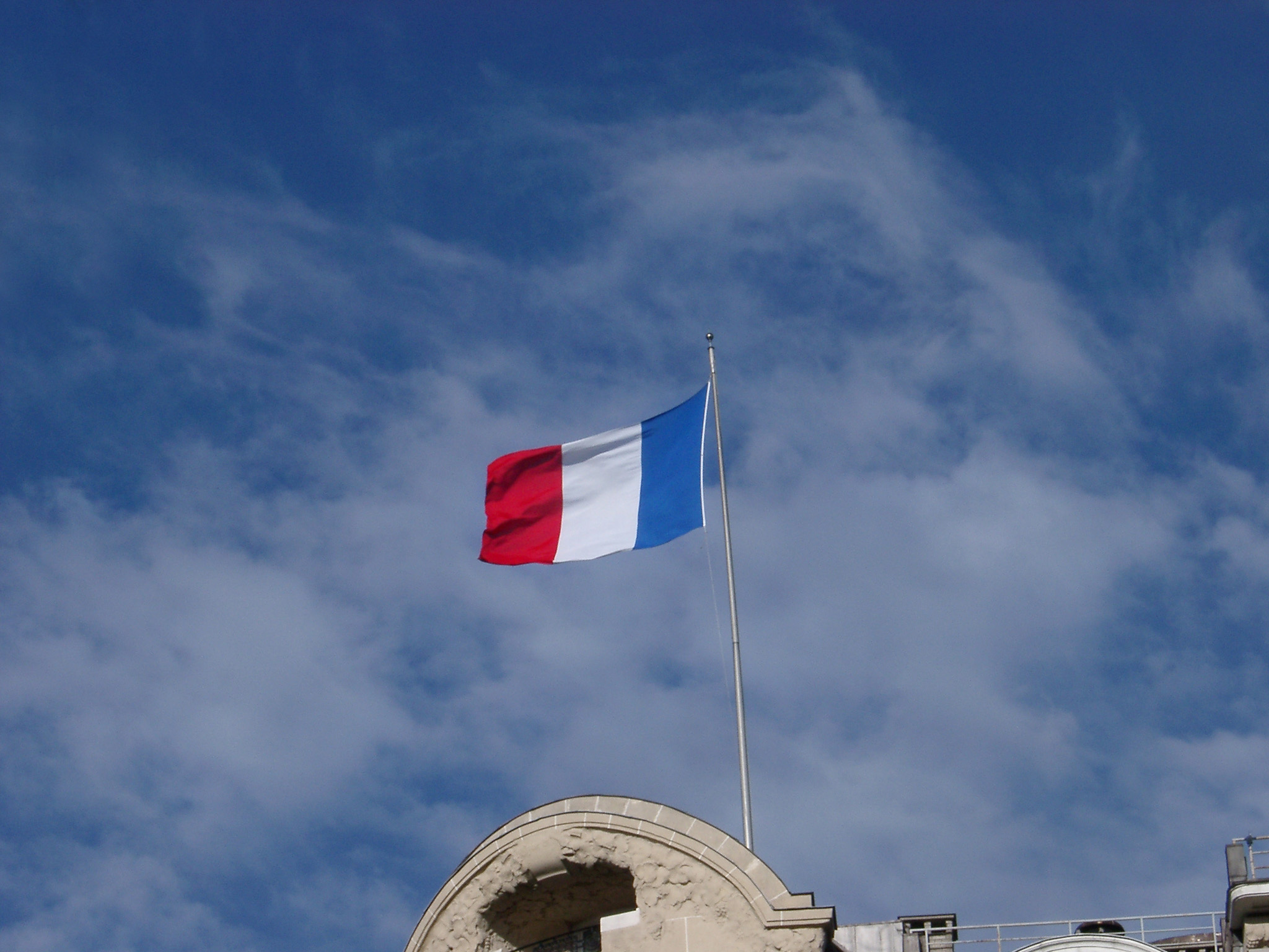 The Tricolor or French National Flag flying from a rooftop against a cloudy hazy blue sky with copyspace
