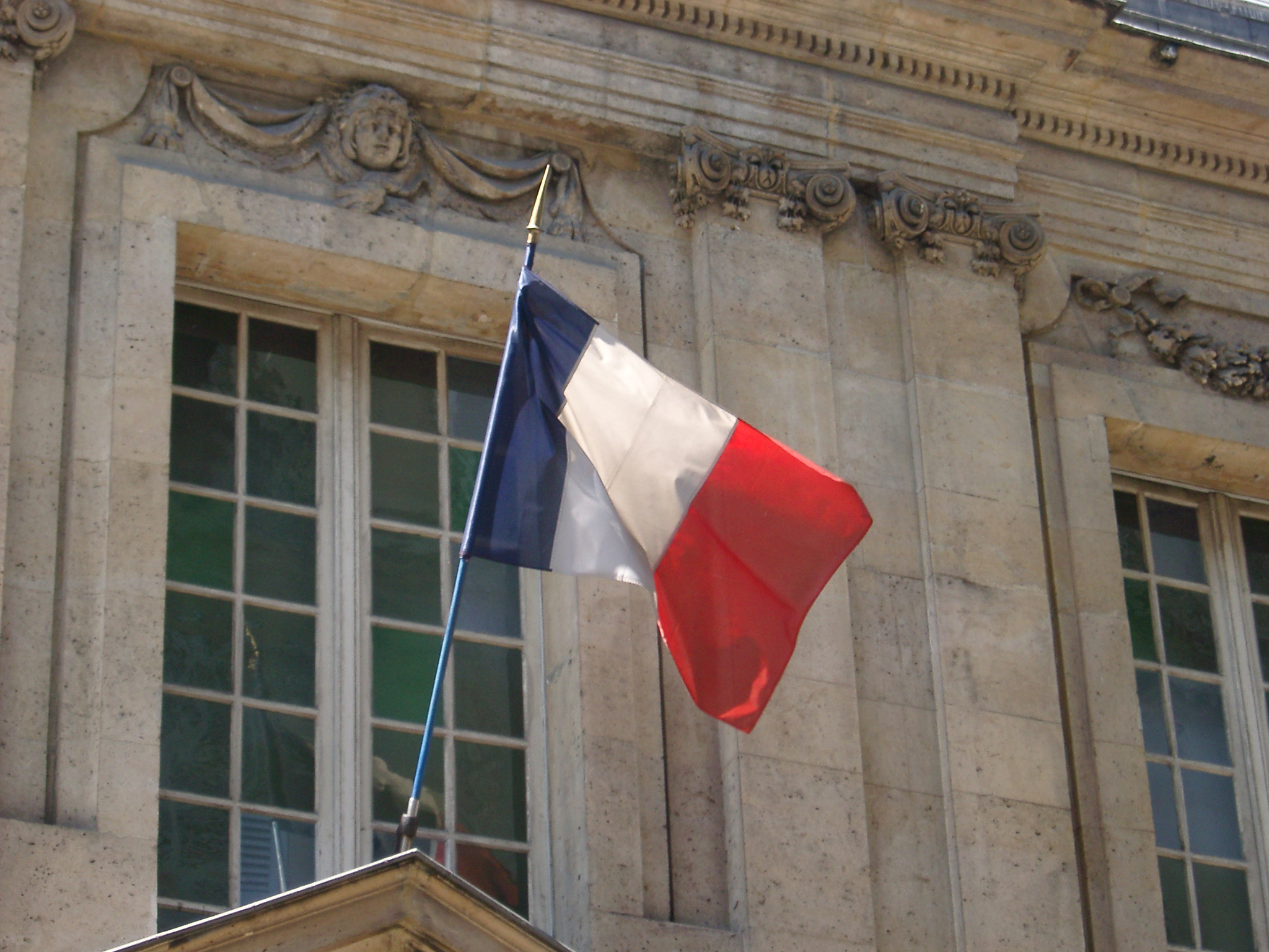 The Tricolor French National Flag in red, white and blue flying from a flagpole on the exterior of an old stone building