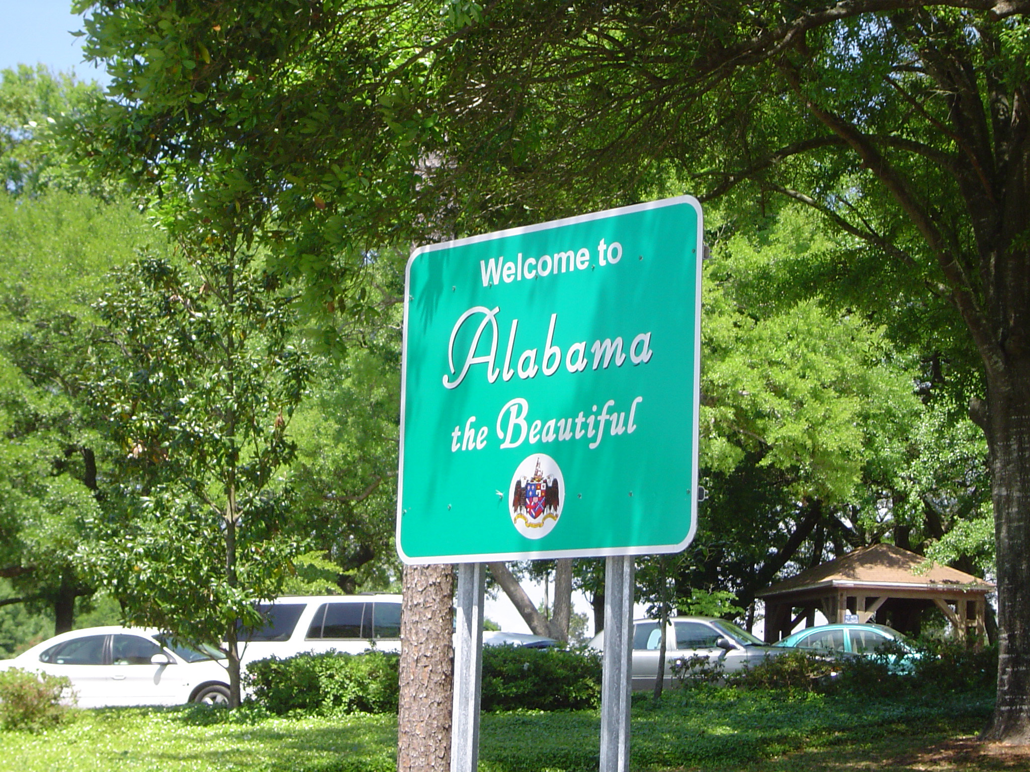 Alabama welcome road sign at the side of a leafy green street conceptual of a road trip vacation driving around the USA