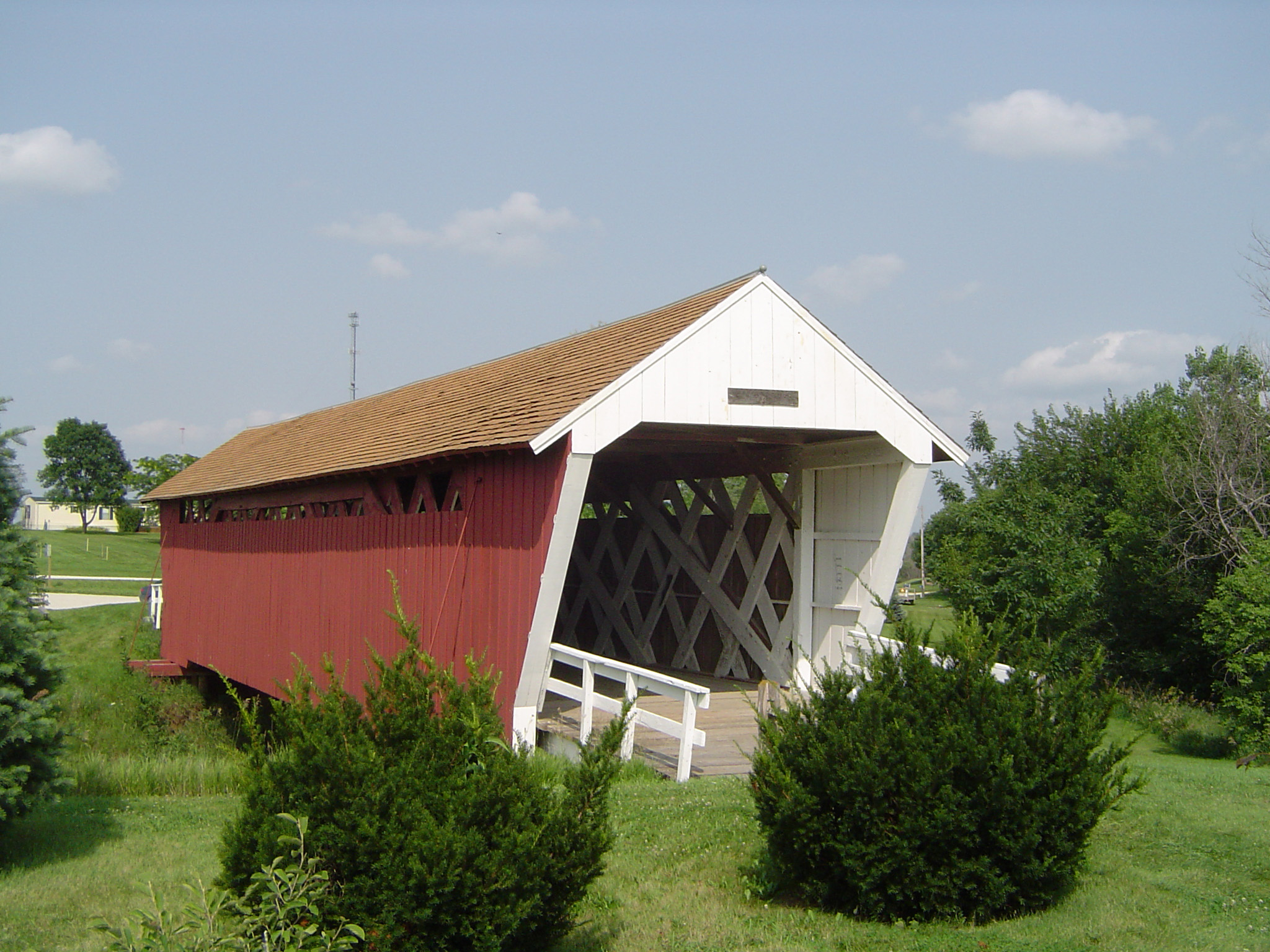 Covered Bridge with Green Grasses and Plants on Sides at Madison County Iowa. Isolated on Light Blue Sky Background.