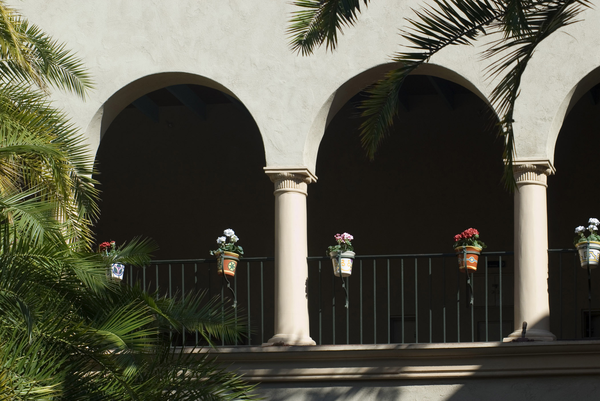 Arched facade decorated with flower pots and tropical palms in Balboa Park, an urban cultural park in San Diego, California,