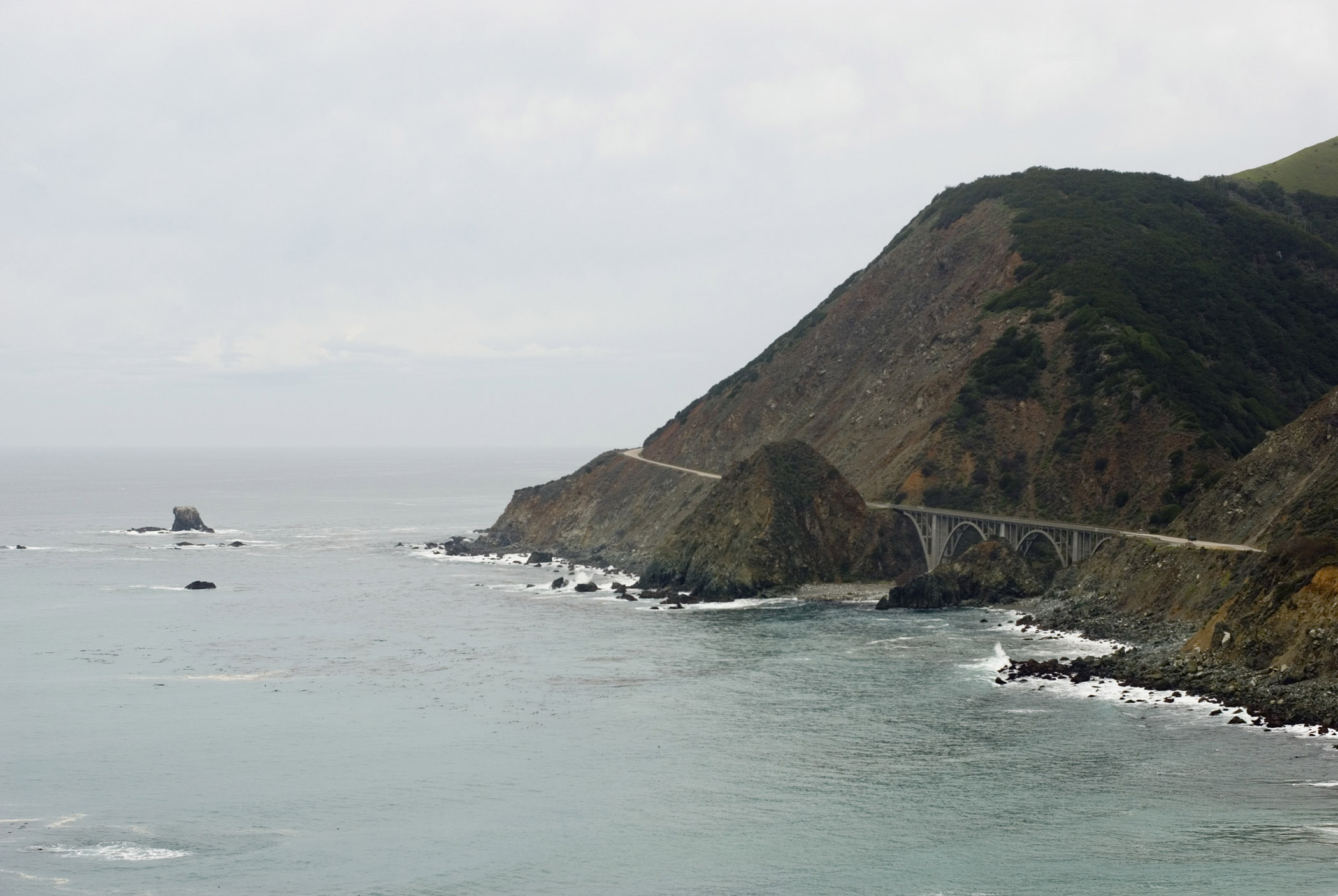 Rocky Big Creek Bridge at Beautiful Big Sur Coast Portrait. Isolated on Lighter Gray Sky Background.