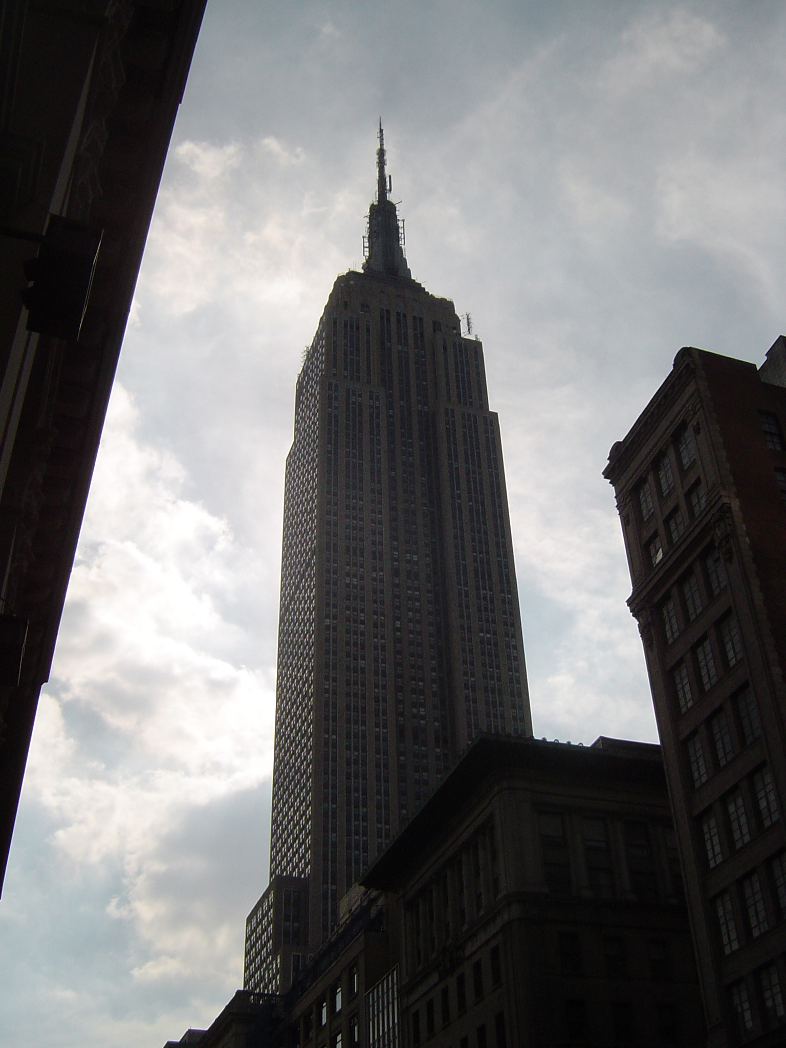 Low angle view looking up of the Empire State Building, Manhattan, New York, silhouetted against a cloudy sky