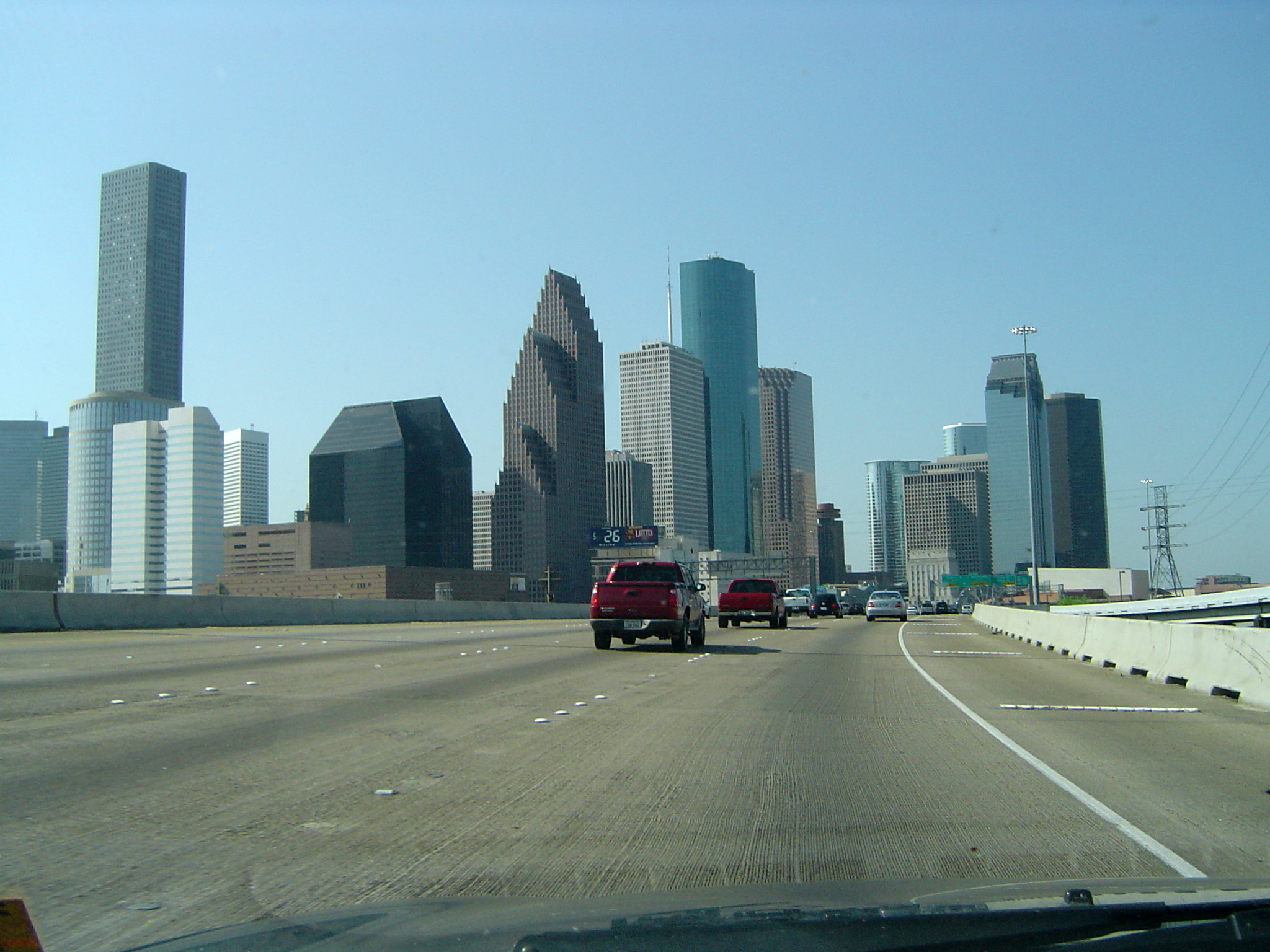Cars driving on a freeway in America towards a city skyline with modern skyscrapers, drivers perspective