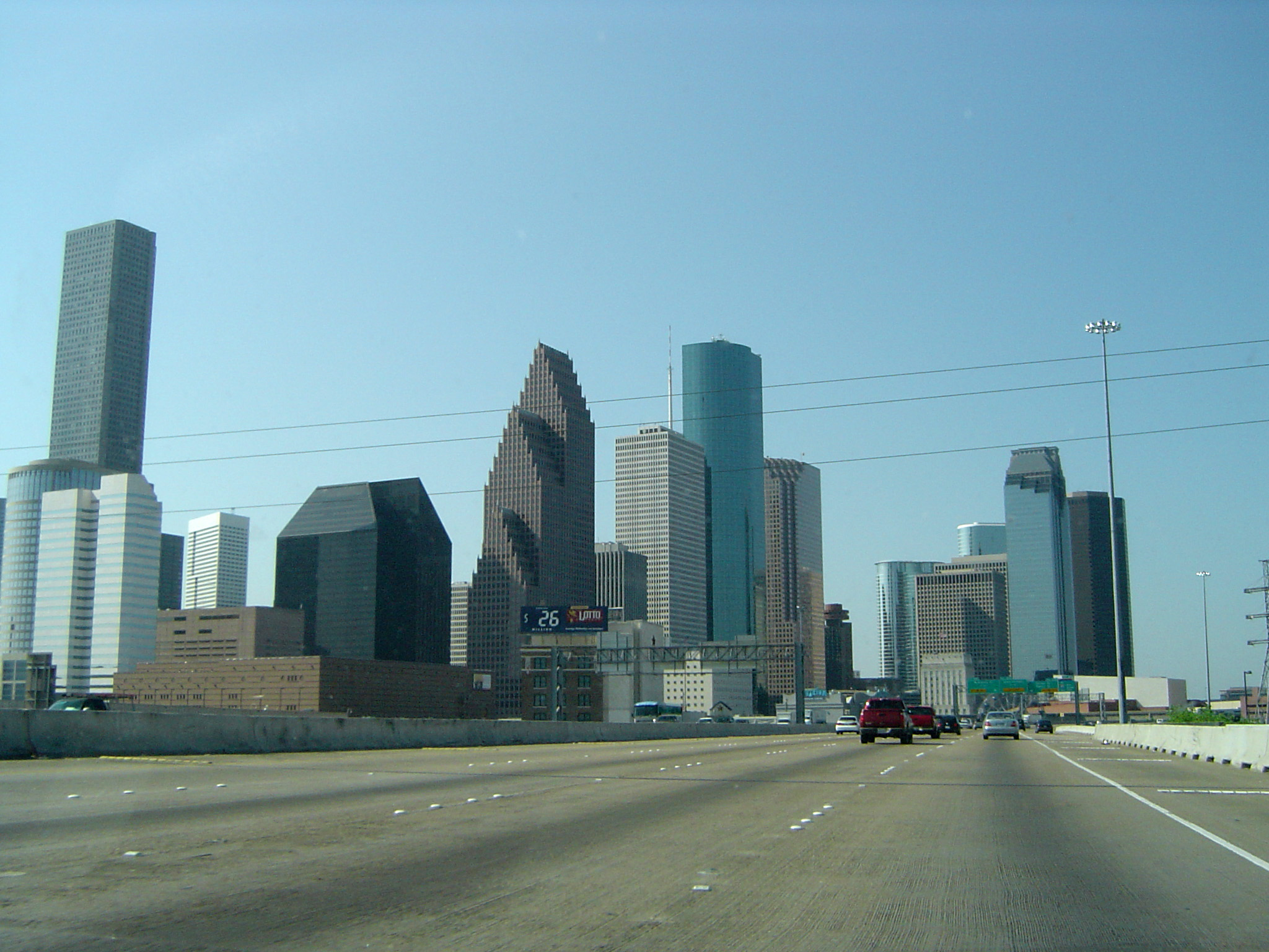 Attractive Architectural Buildings Along Freeway on Light Blue Sky Background.