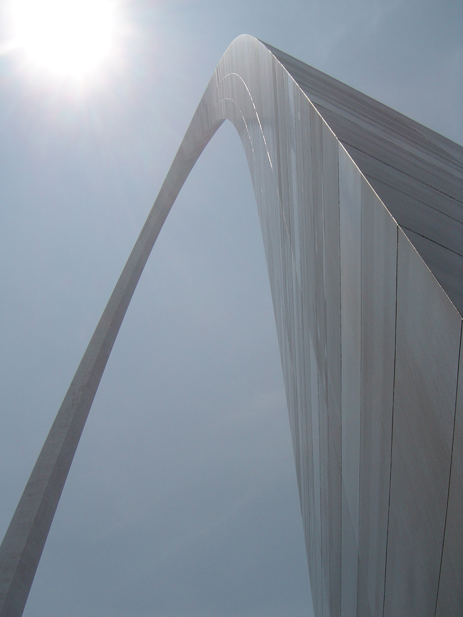View looking up the curve of the Gateway Arch, St Louis, USA against a blue sky with sunburst