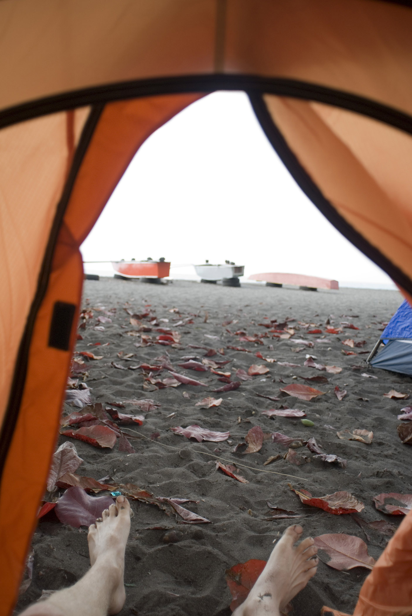 Big Island camping with a view of a mans feet in the opening of an orange tent with a background of a volcanic beach and canoes