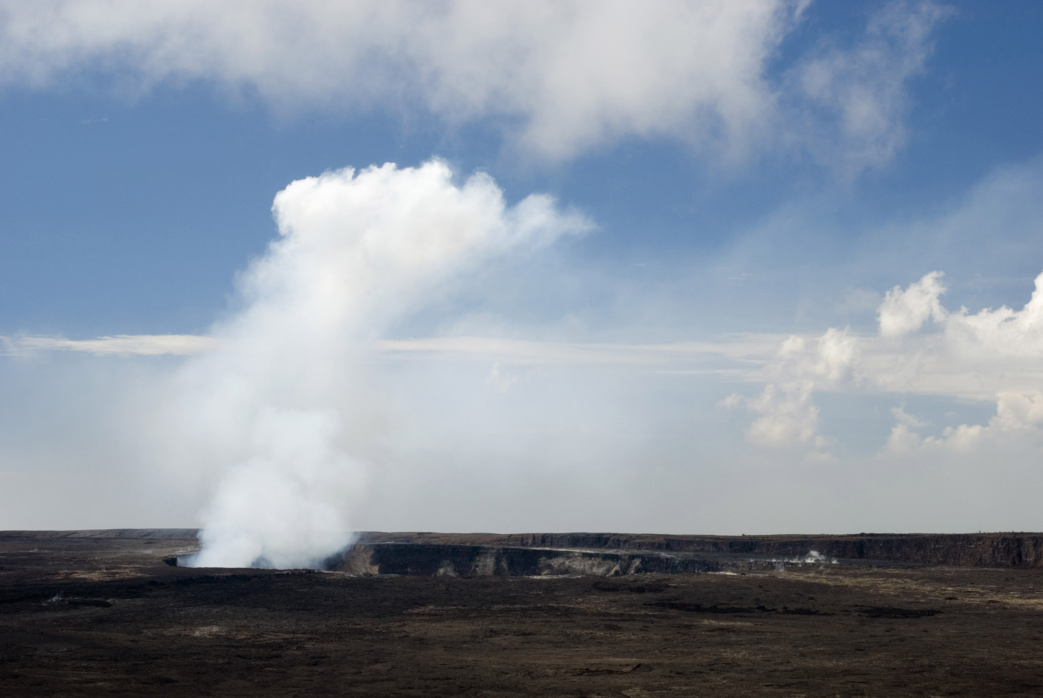 Smoke at Kilauea Caldera in Hawaii. An Active Volcano in Hawaiian Islands. Isolated Blue and White Clouds.
