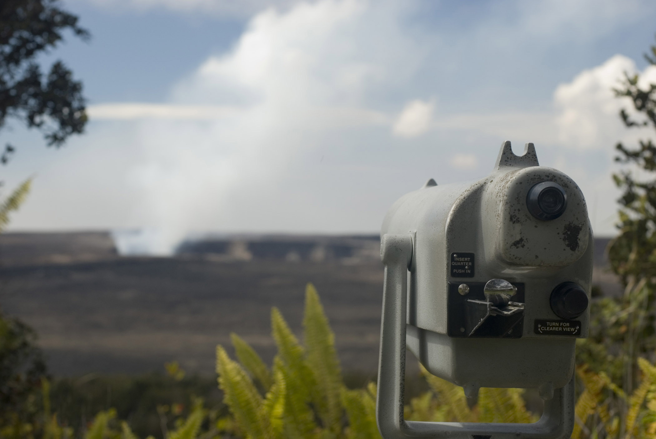 Telescope overlooking the Kikauea Crater with the Haleamaumau crater in the center of the Kilauea caldera releasing smoke and steam - the heart of Kilauea volcano