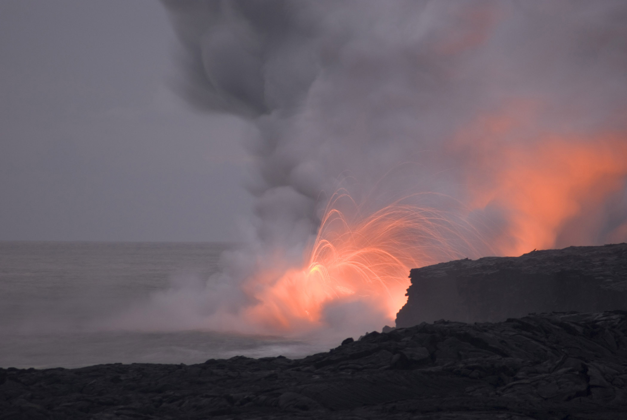 Red hot lava exploding from a volcanic fissure in an eruption on an active volcano on Hawaii, USA