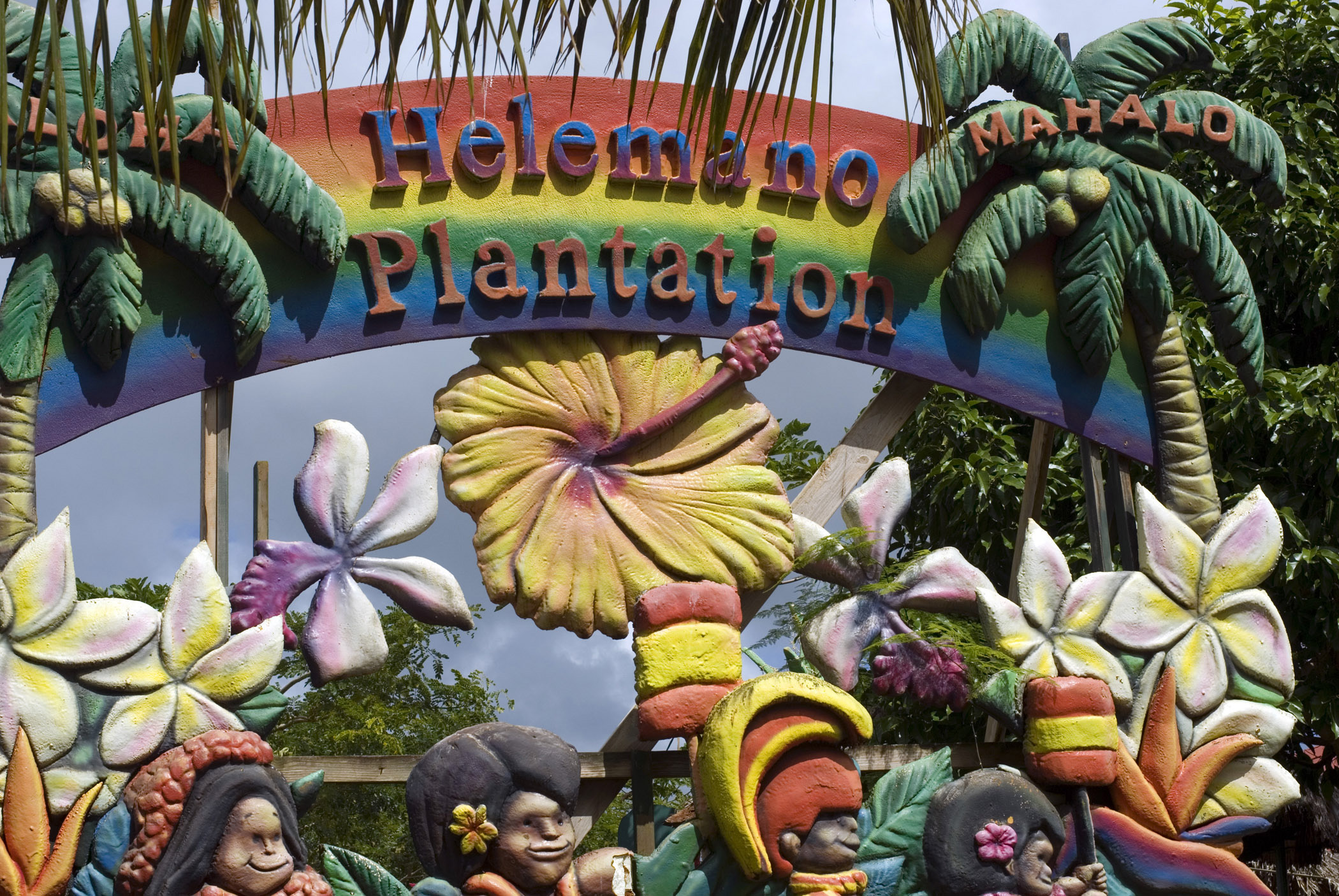 Colorful Helemano Plantation sign on a pineapple plantation visitor center in Hawaii with palm trees, frangipani and hibiscus flowers and peoples faces