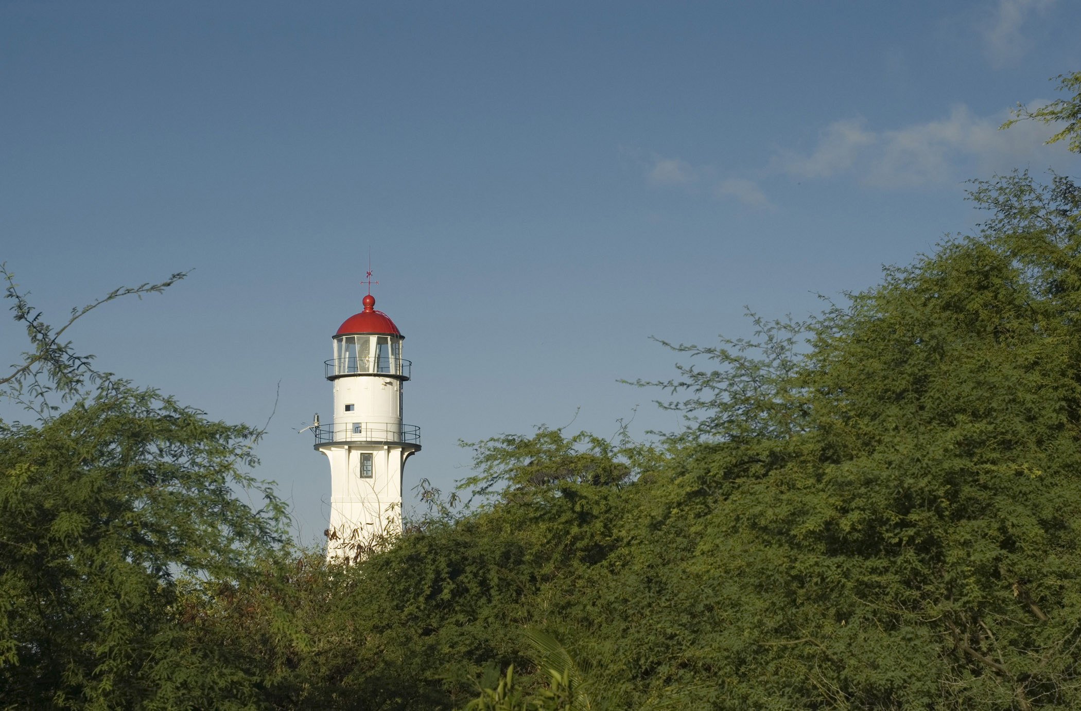 View across green vegetation of the lamp and tower of the Diamond Head Lighthouse, Honolulu, Hawaii