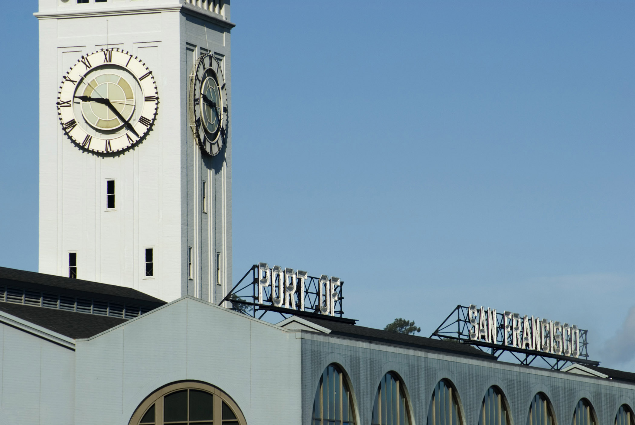 Exterior Wall Clock on Building at Embarcadero San Francisco on Light Blue Sky Background.